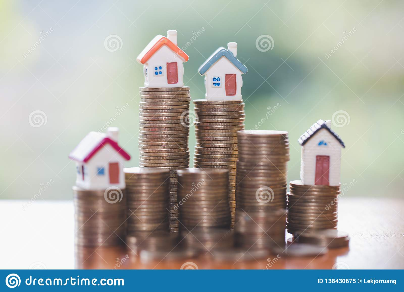 A mini casa na pilha de moedas, organismos de investimento imobiliário, salvar o dinheiro com investimento da moeda da pilha, do