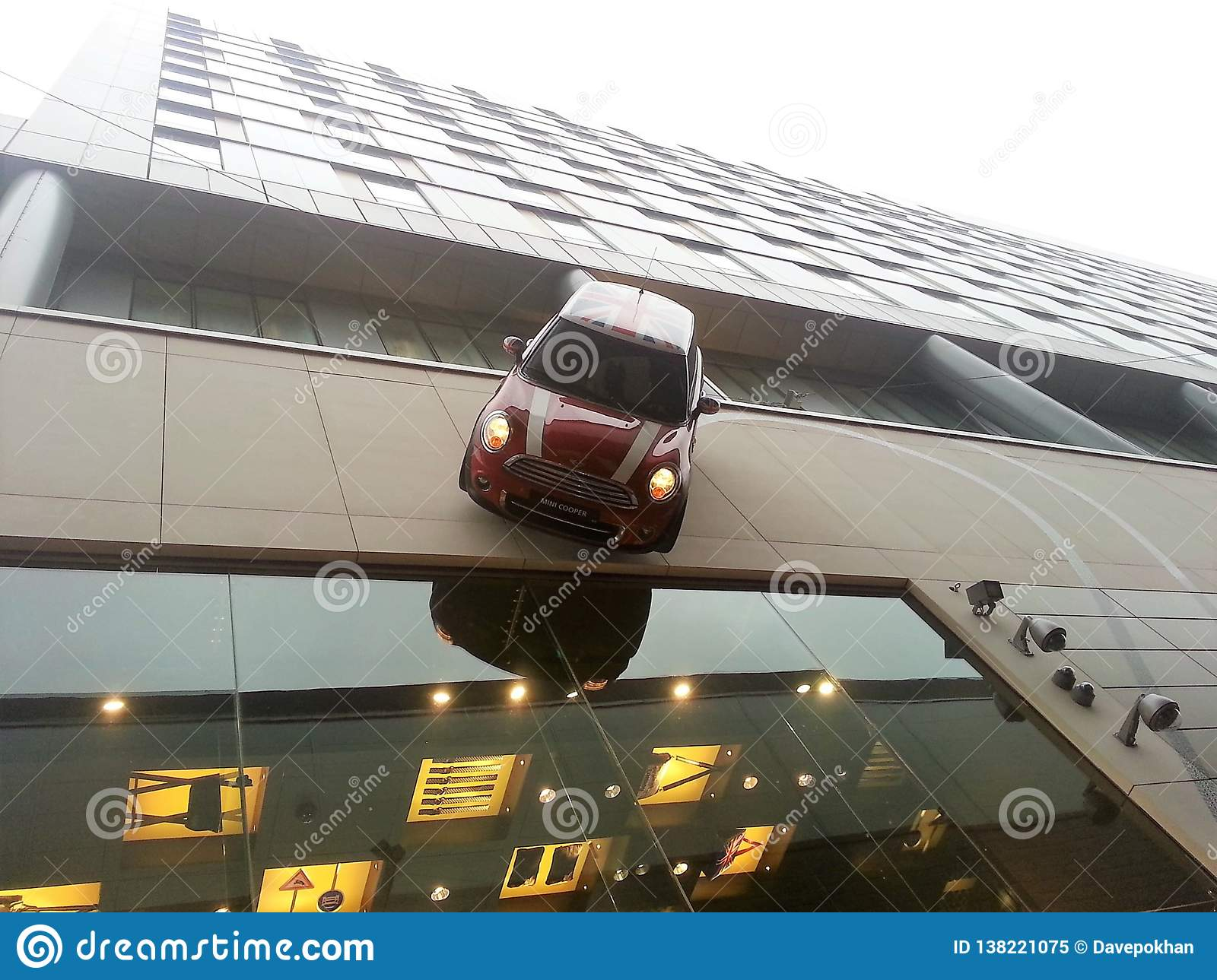 Mini Cooper driving down side of building