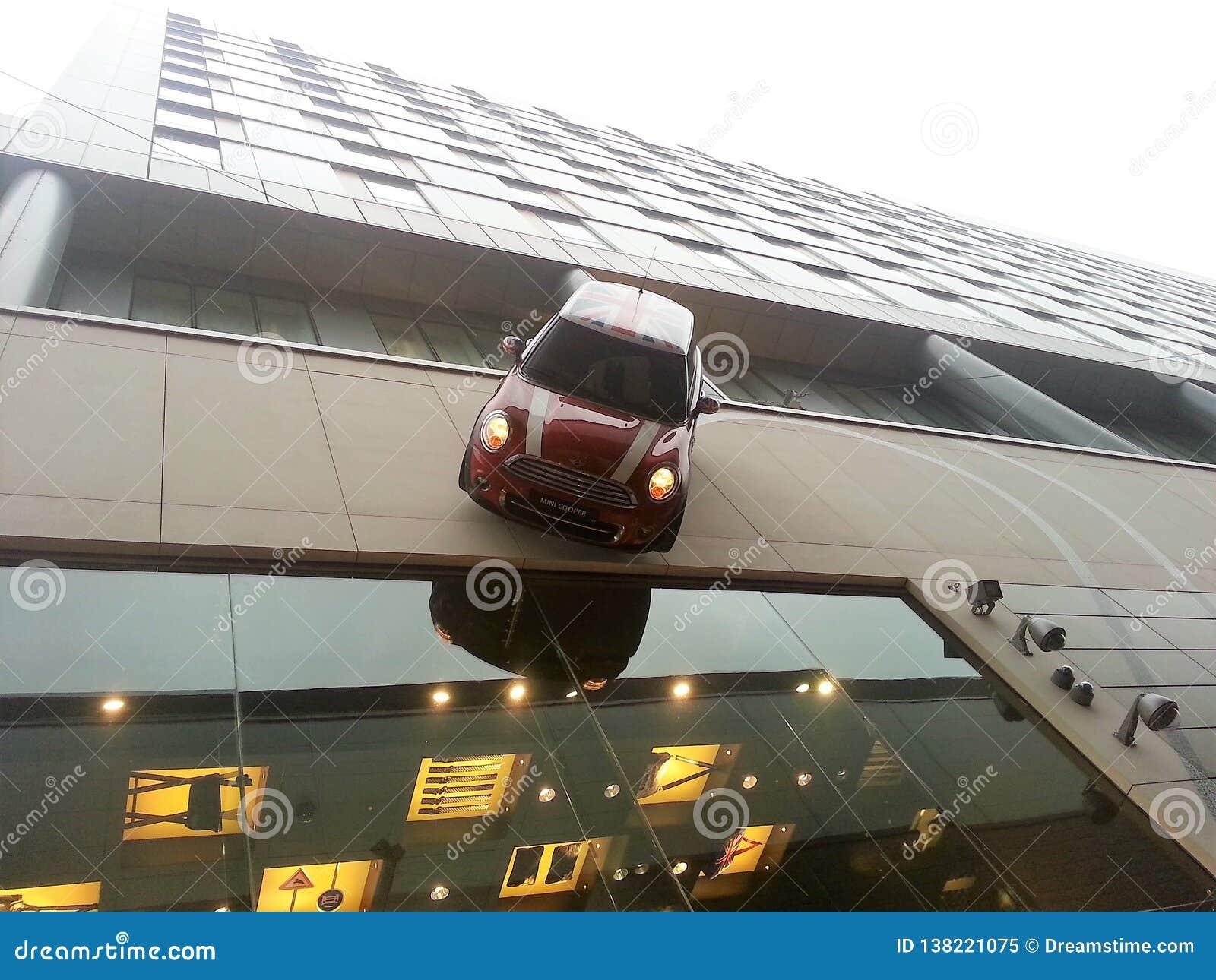 Mini Cooper que conduz abaixo do lado da construção