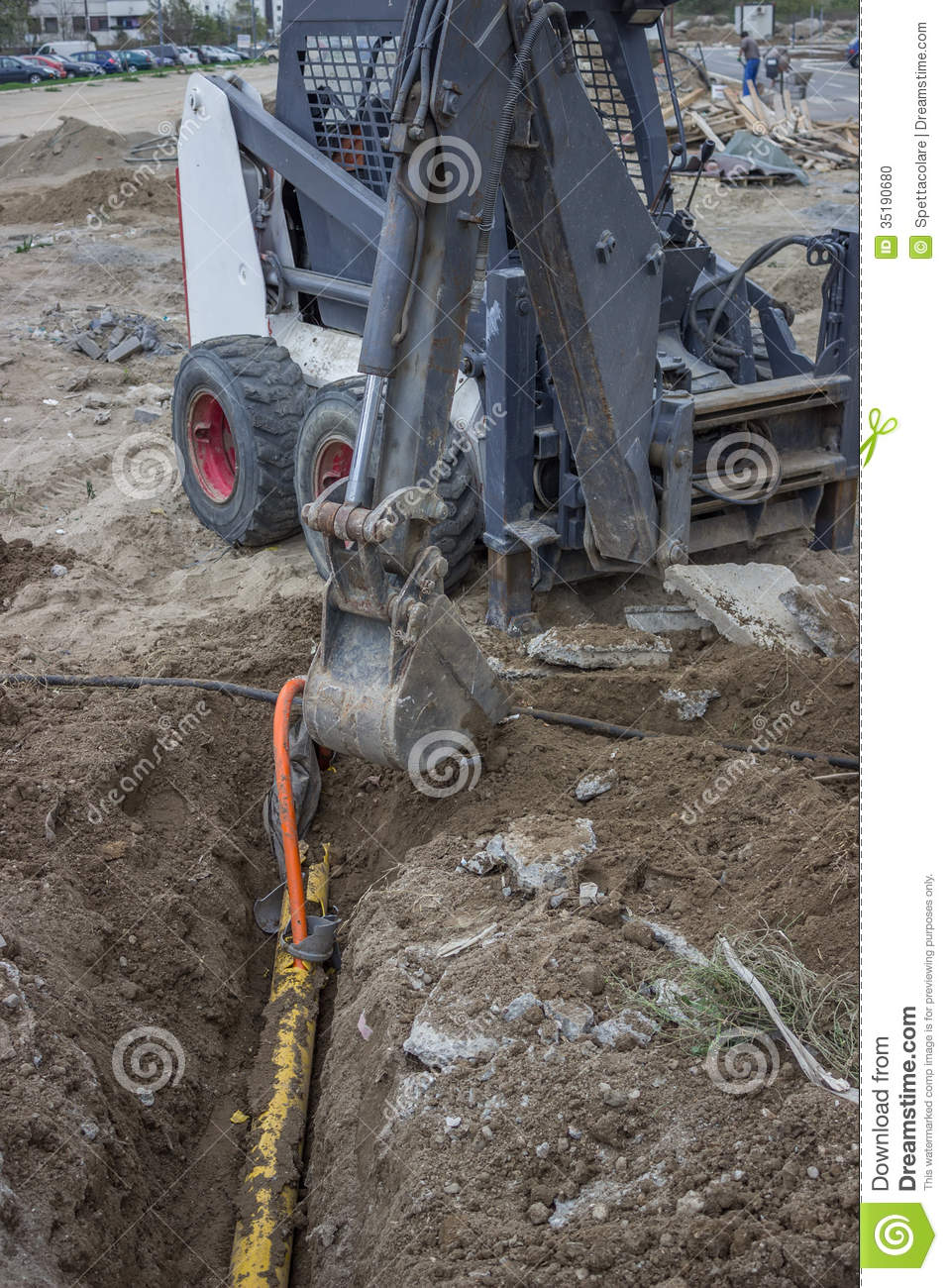 Mini Excavator Digging Up A Electrical Cables From Trench