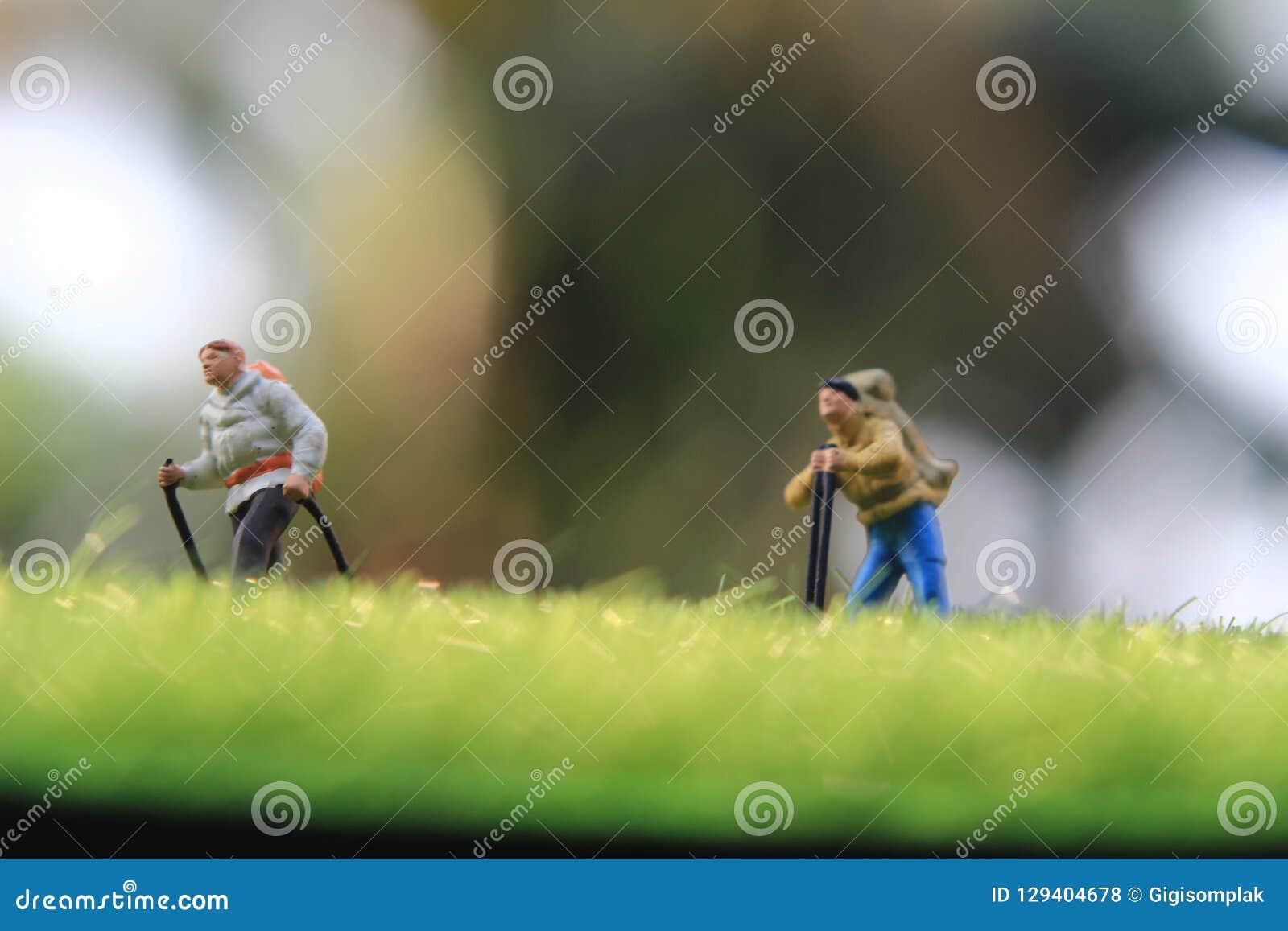 Mini Figure Hiker, caminando en el campo de hierba,