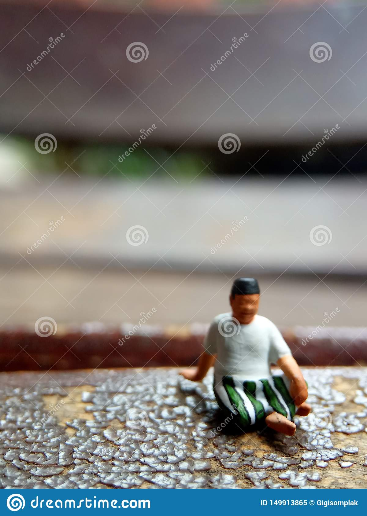 Mini figure toy old man sit at scratch wooden chair, with copy or negative space for text placement area