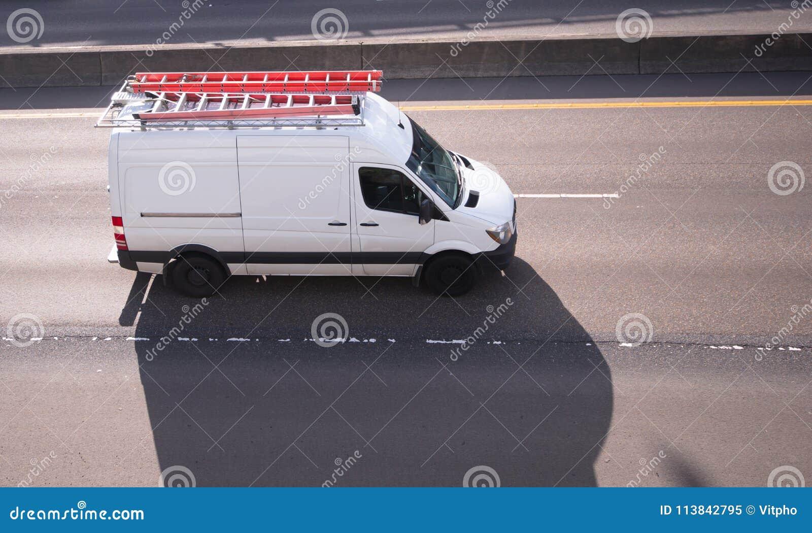 Mini furgone del carico commerciale con i capi lunghi sul funzionamento del tetto
