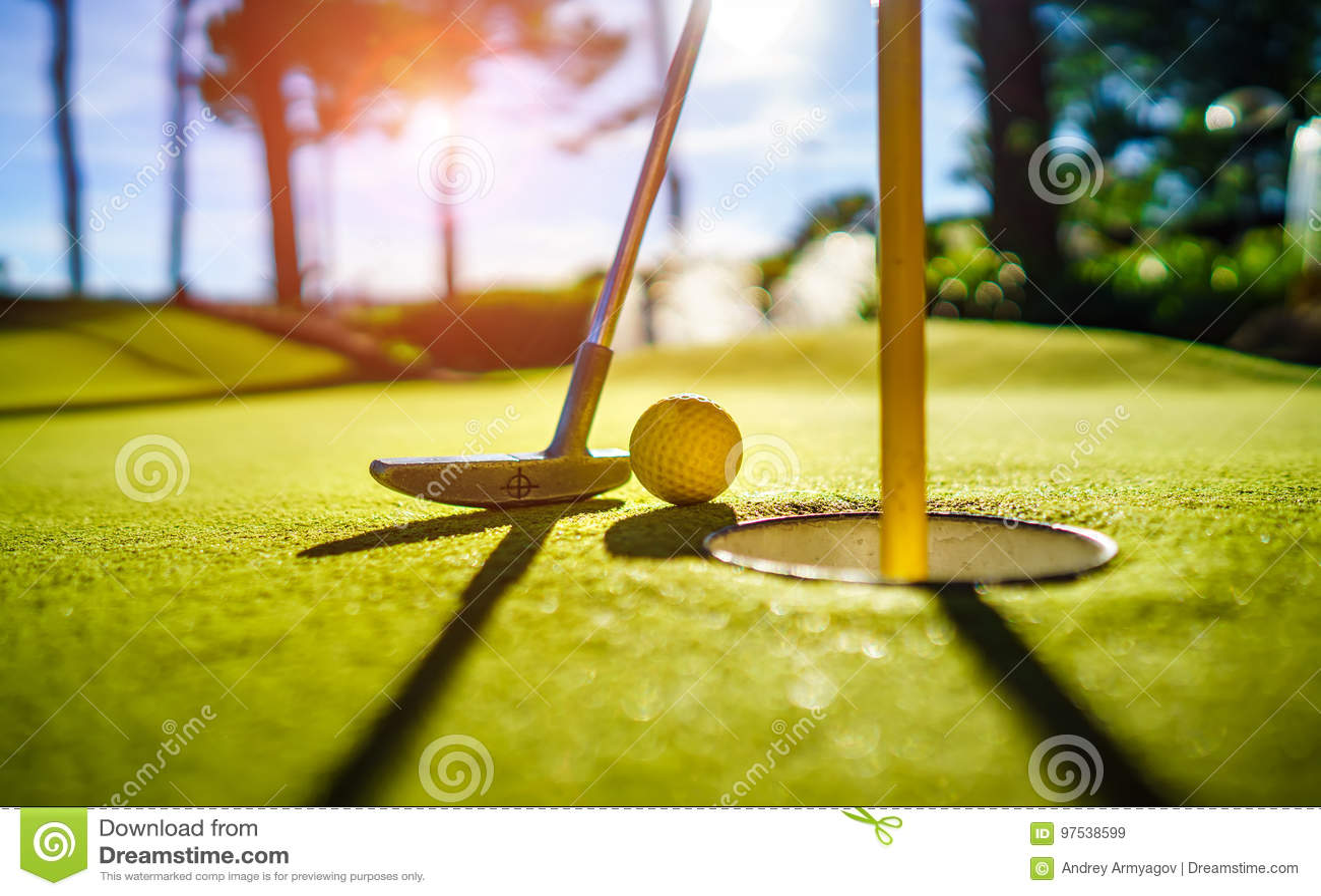 Mini Golf jaunissent la boule avec une batte près du trou au coucher du soleil