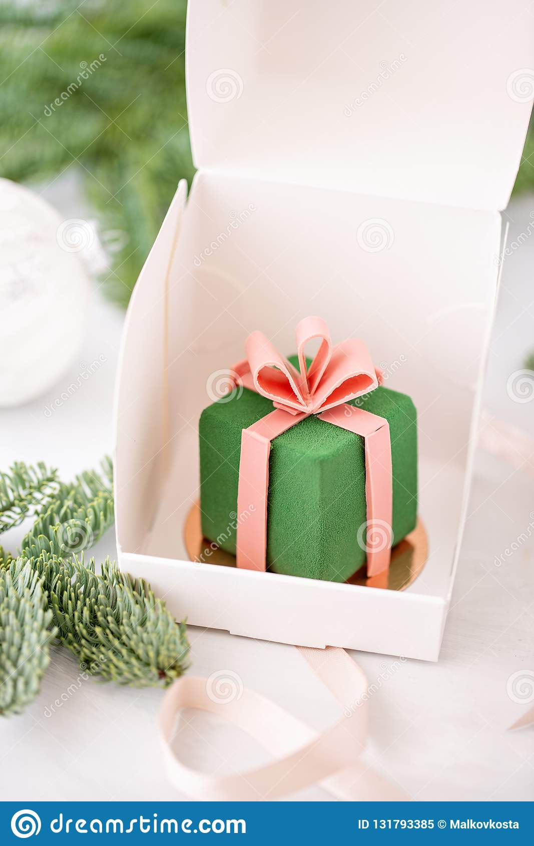 Mini mousse pastry dessert covered with green velour. Individually wrapped in white box. The branches of spruce on bokeh