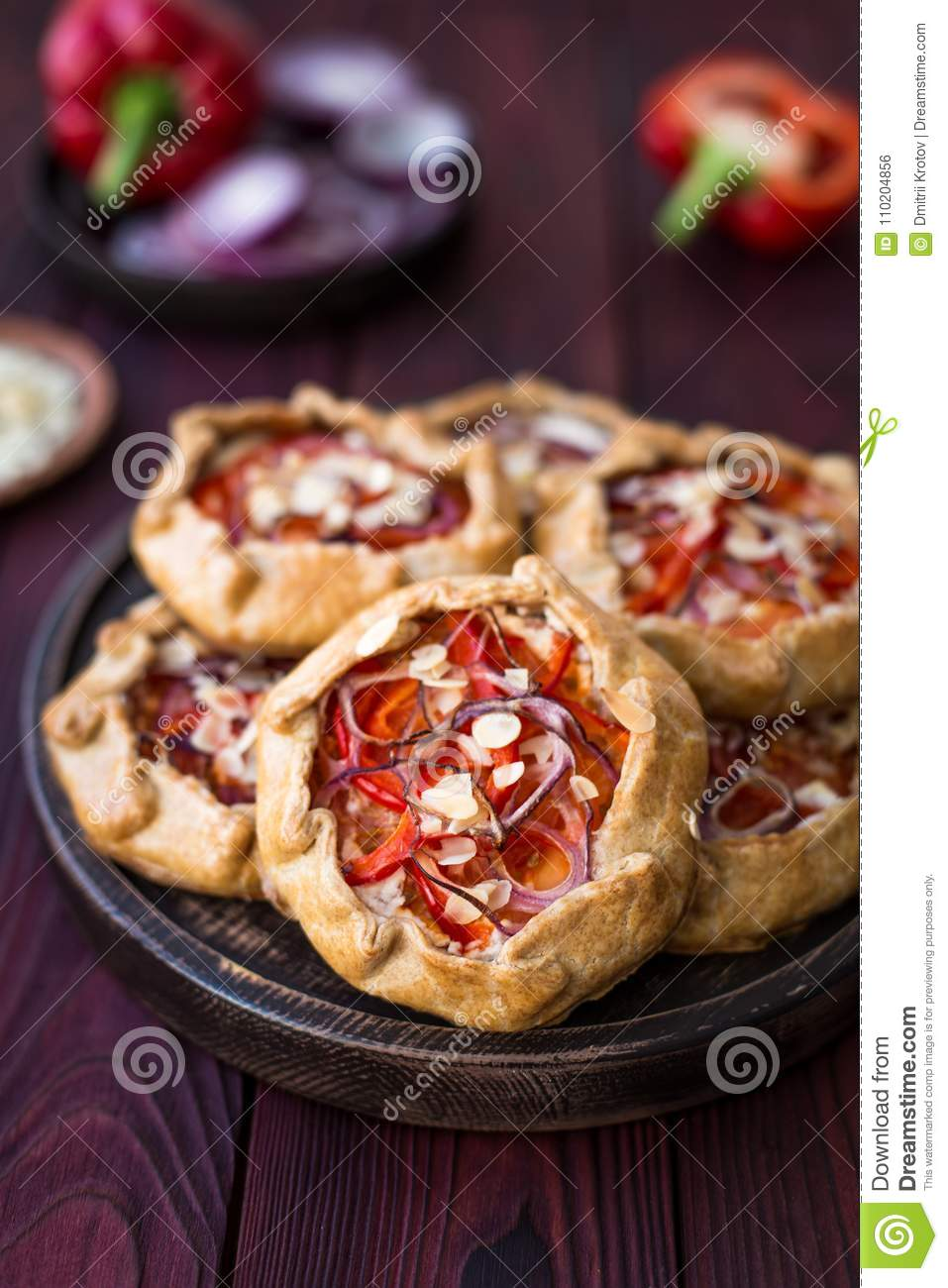 Mini pizza, vegetable galette with cream cheese, red onion, tomatoes, sweet pepper and almonds