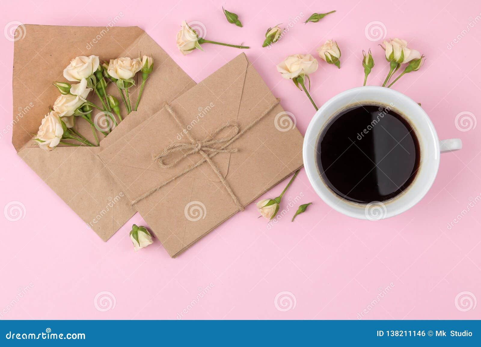 Mini rosas bonitas um a xícara de café e um envelope em um fundo cor-de-rosa brilhante feriados Dia do `s do Valentim Dia do `s d