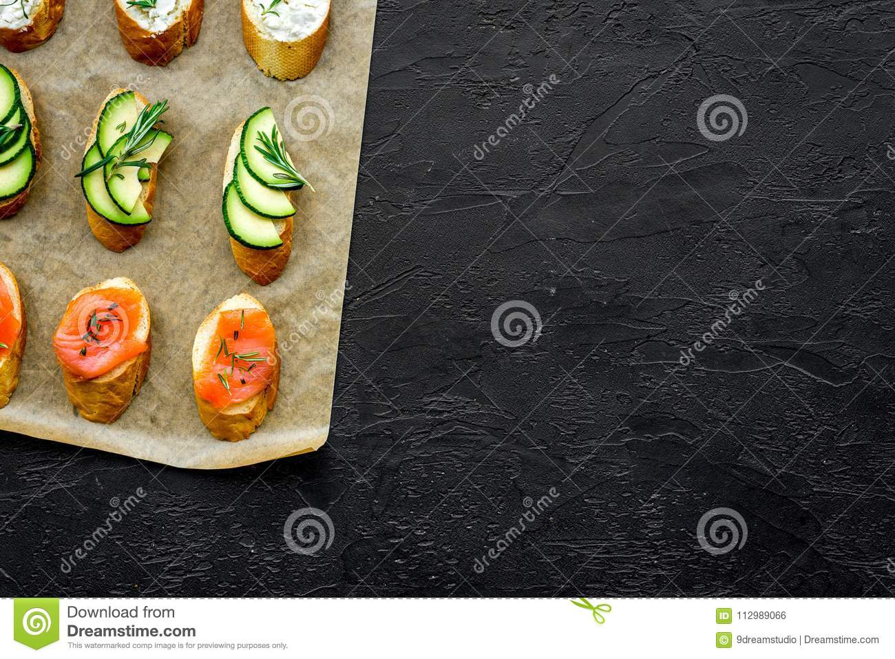 Mini sandwich set with french baguette, cheese, fish and avocado on black background top view mock up