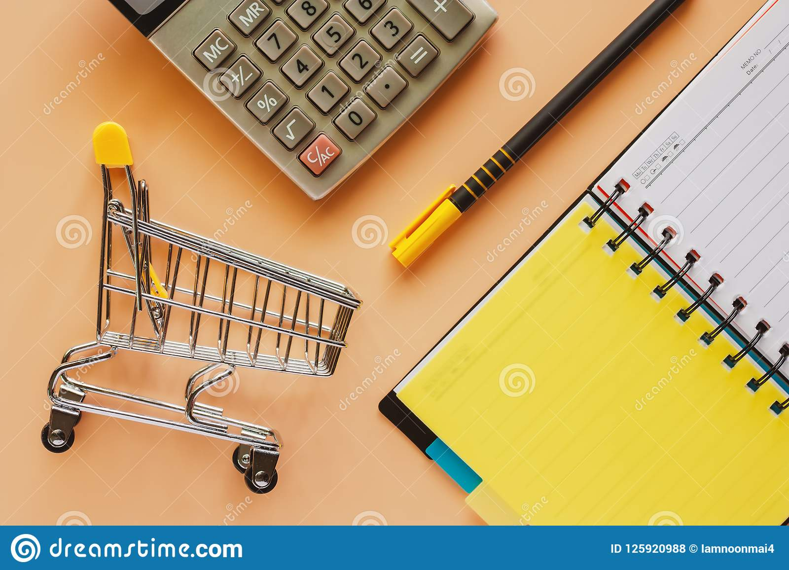 Mini shopping cart or trolley with opened spiral notebook, pen a