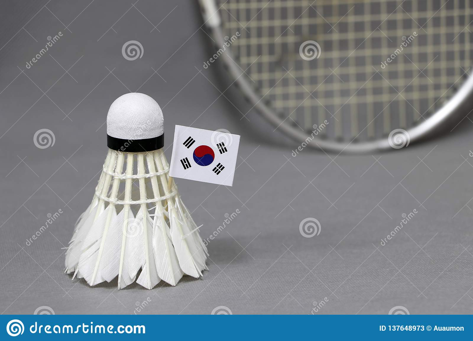 Mini South Korea flag stick on the white shuttlecock on the grey background and out focus badminton racket