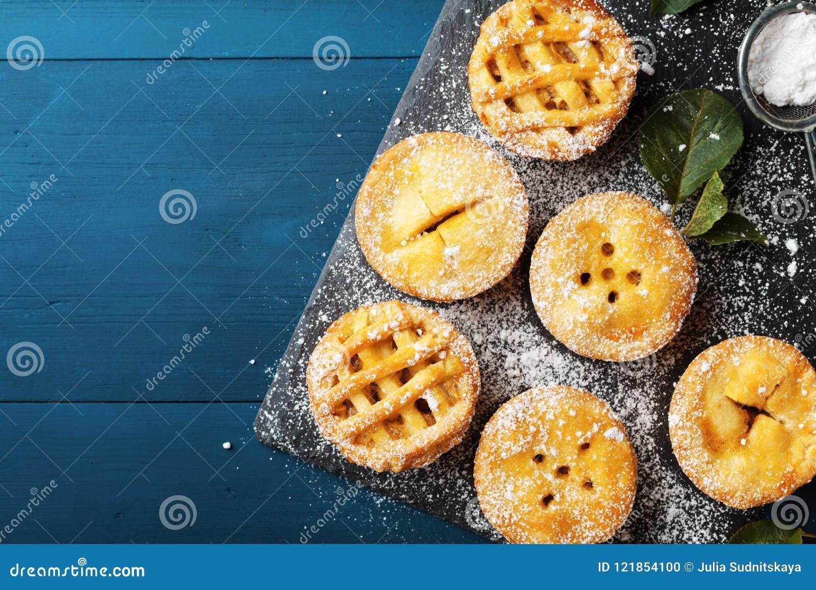 Mini tortas de maçã deliciosas no fundo azul de cima de Sobremesas da pastelaria do outono