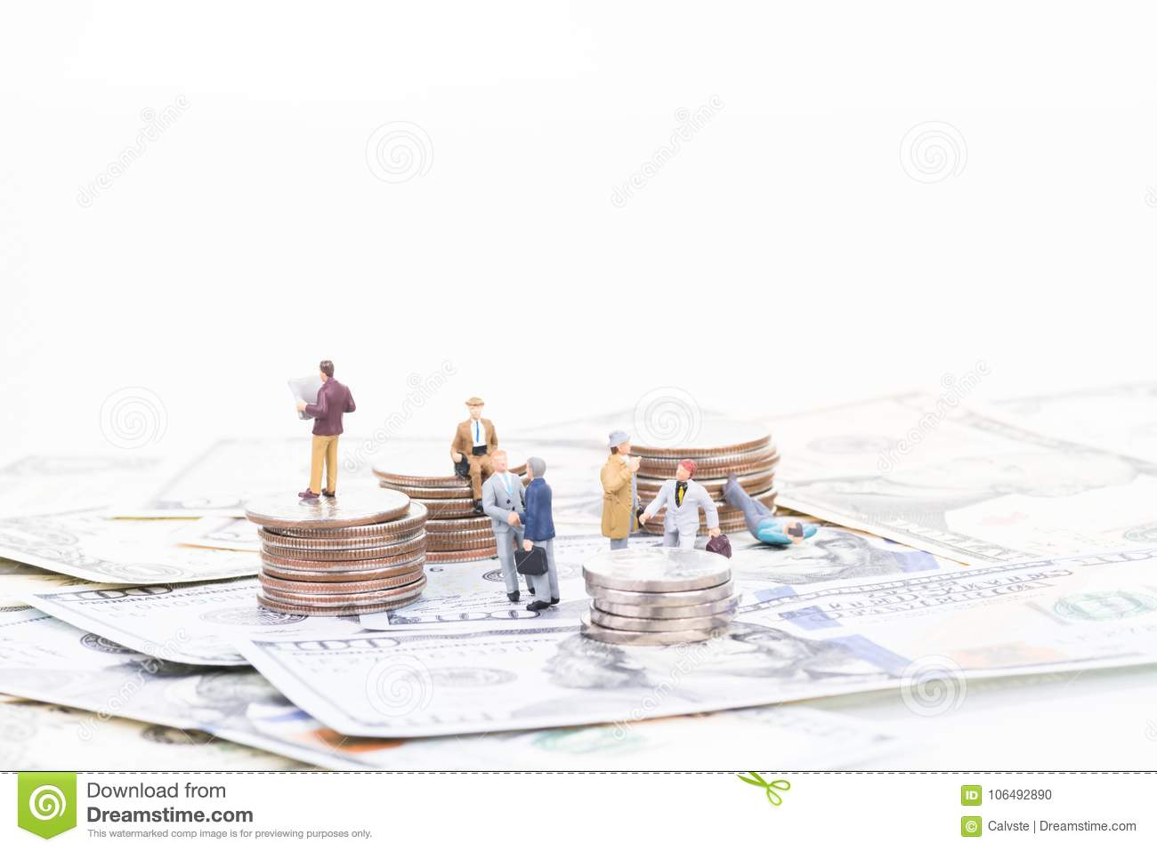 Miniature business people on US banknotes and coins
