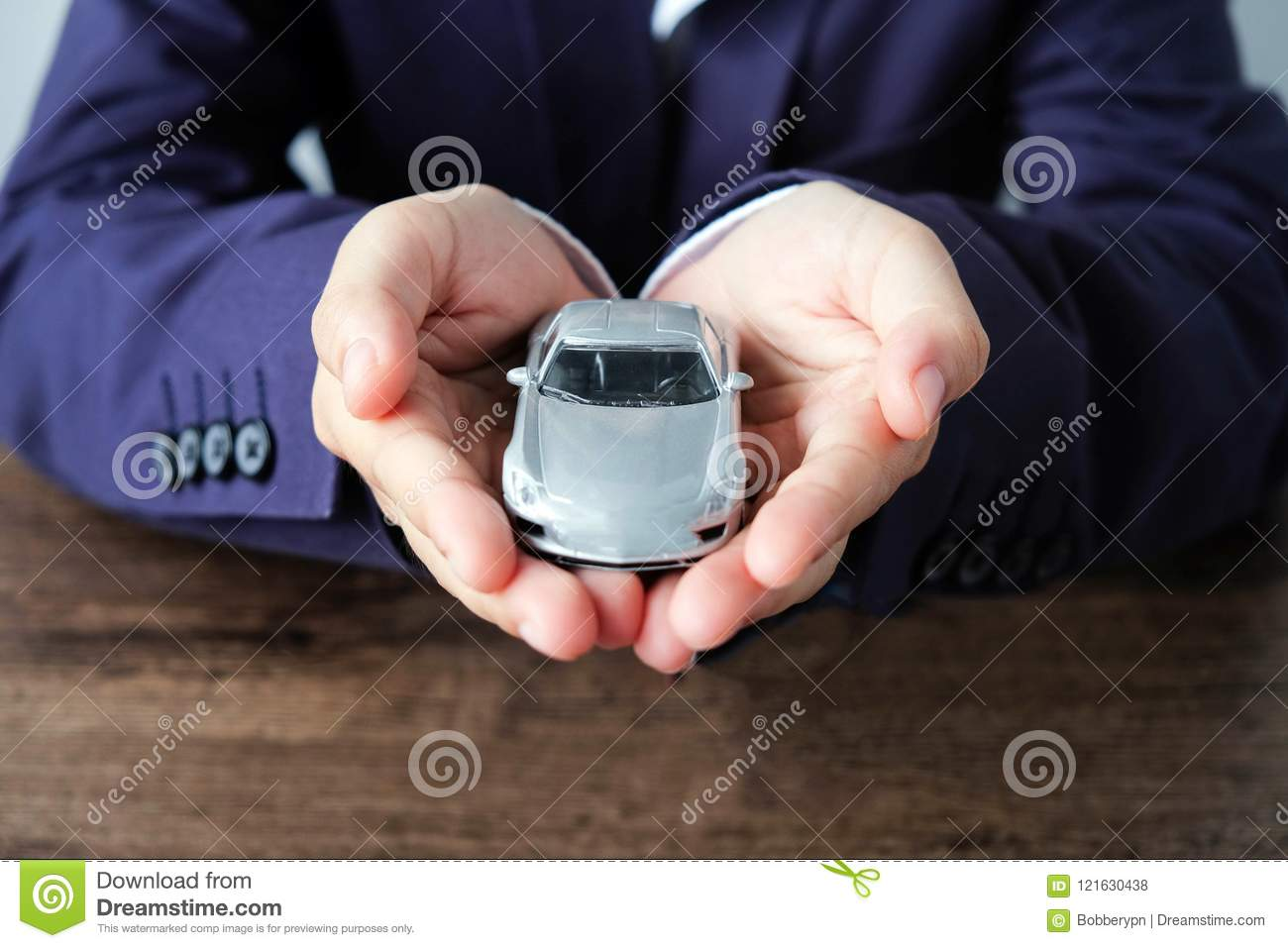 Miniature car model on hand, Auto dealership and rental concept
