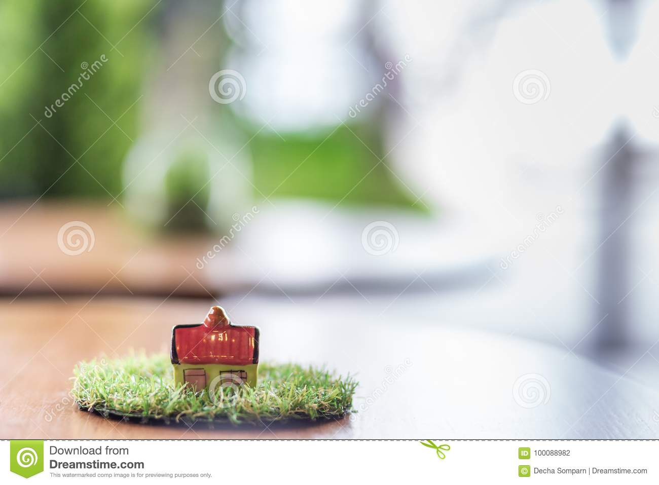 Miniature ceramic house on wooden mock up over blurred green garden on day noon light