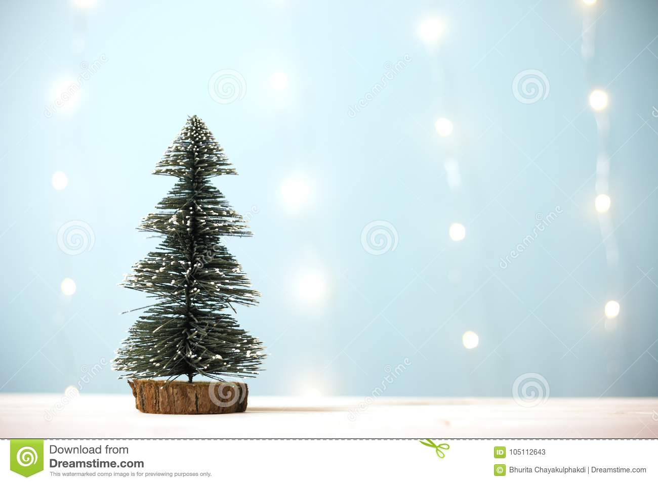 download miniature christmas tree on wooden table over blur bokeh light blue background stock image