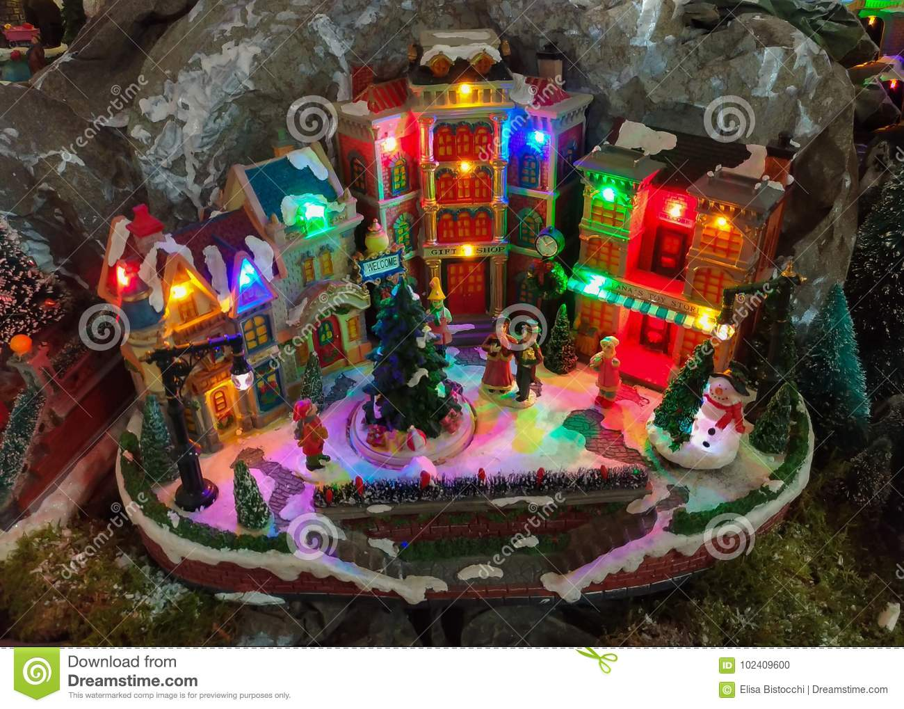 miniature christmas village with colored lights at santa claus village shop in terni
