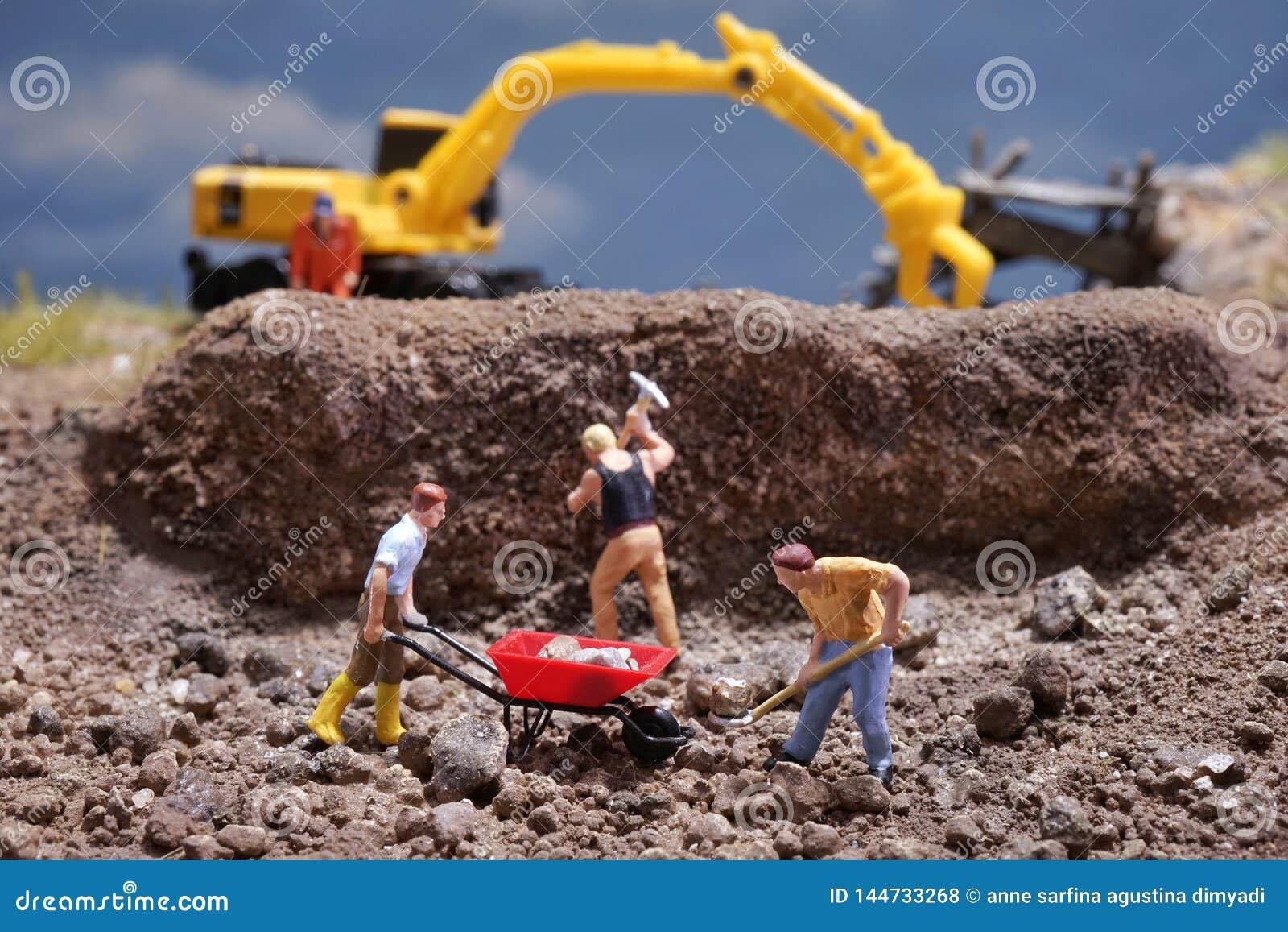 MiniatureContruction arbetare som arbetar lyftande stenen genom att använda skyffeln