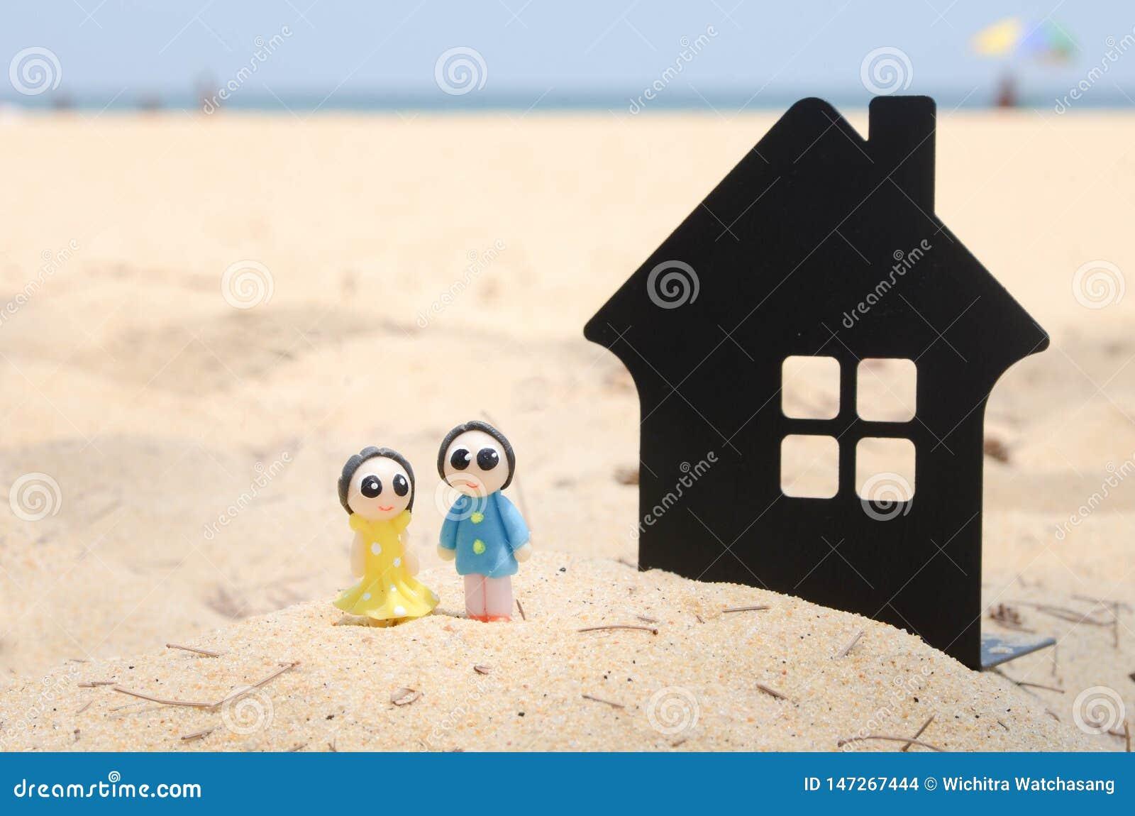 miniature couple and miniature house on the beautiful beach