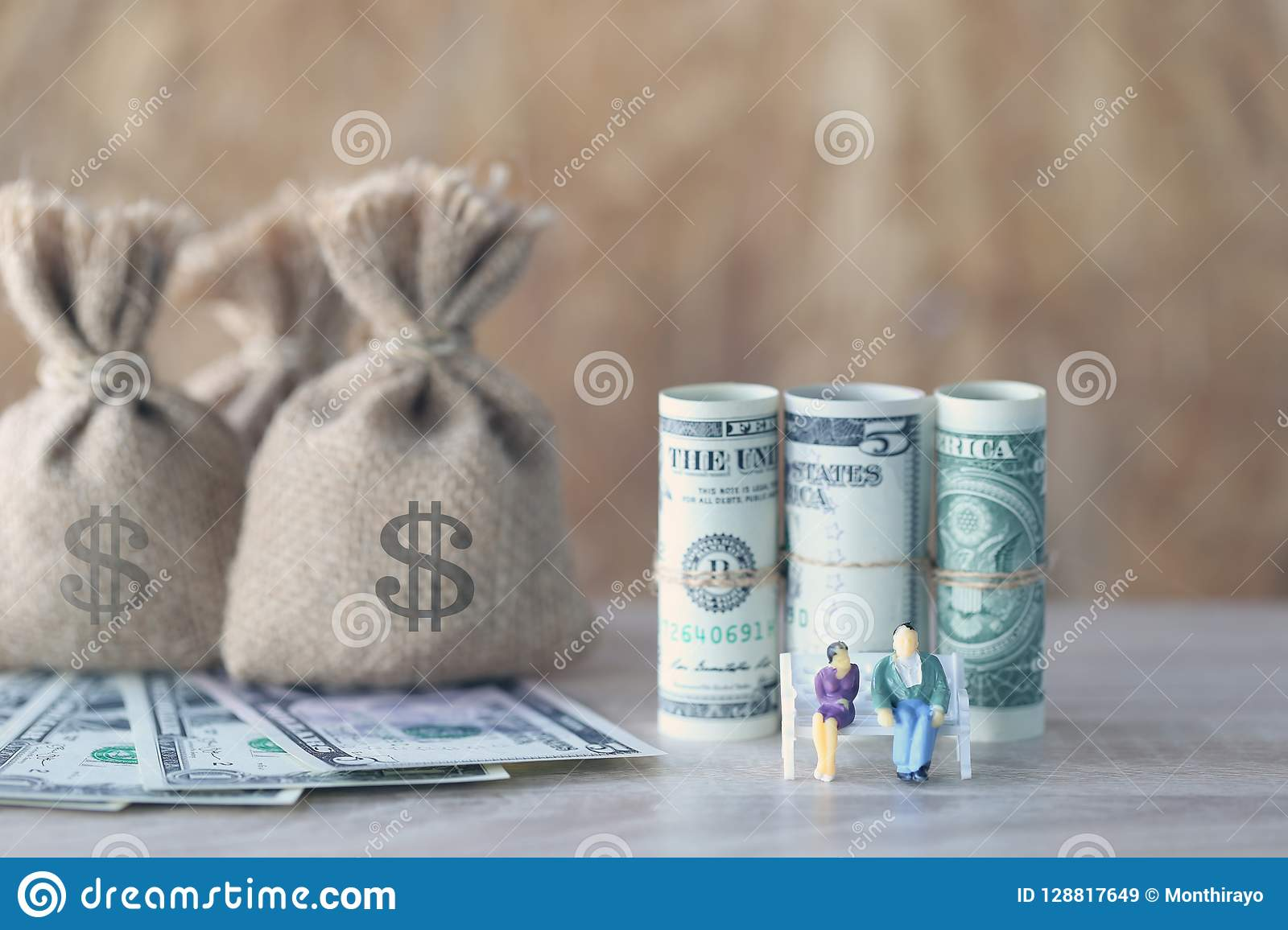 Miniature couple standing on the chair and money bag with banknote on wooden background, Save money for prepare in future and