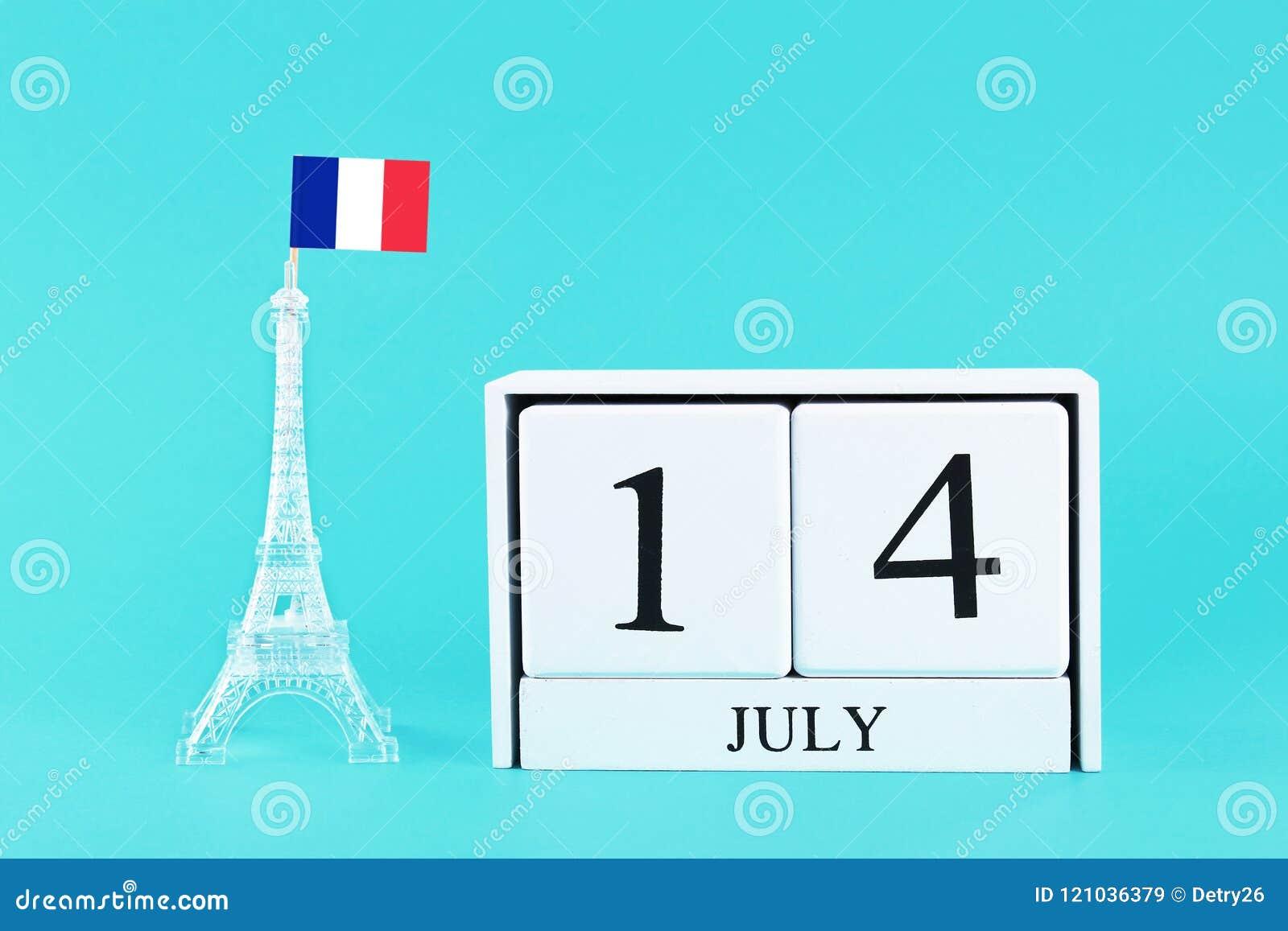 Miniature de Tour Eiffel avec un drapeau français et de calendrier en bois sur un fond bleu Le concept des vacances est le 14 jui