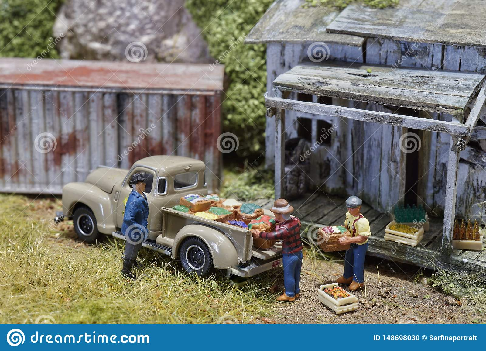 Miniature of farmer looking at workers carrying product goods to car pick up in distribution warehouse factory.