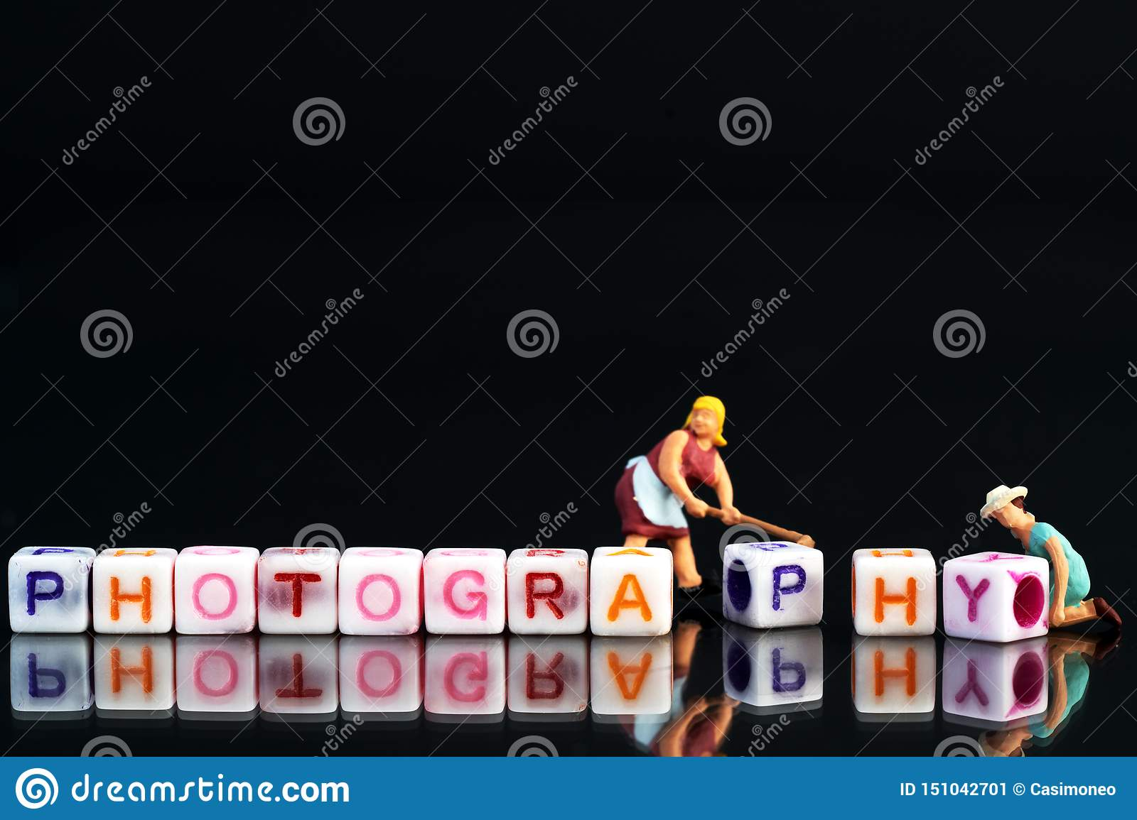 Miniature figurine woman fixing adjusting a Group Of Letters forming Words Spelling