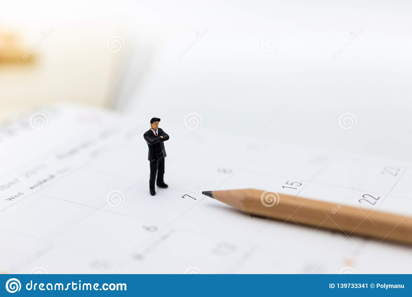 Miniature people : Businessman standing on the calendar to set the date for the meeting . Image use for business meetings concept