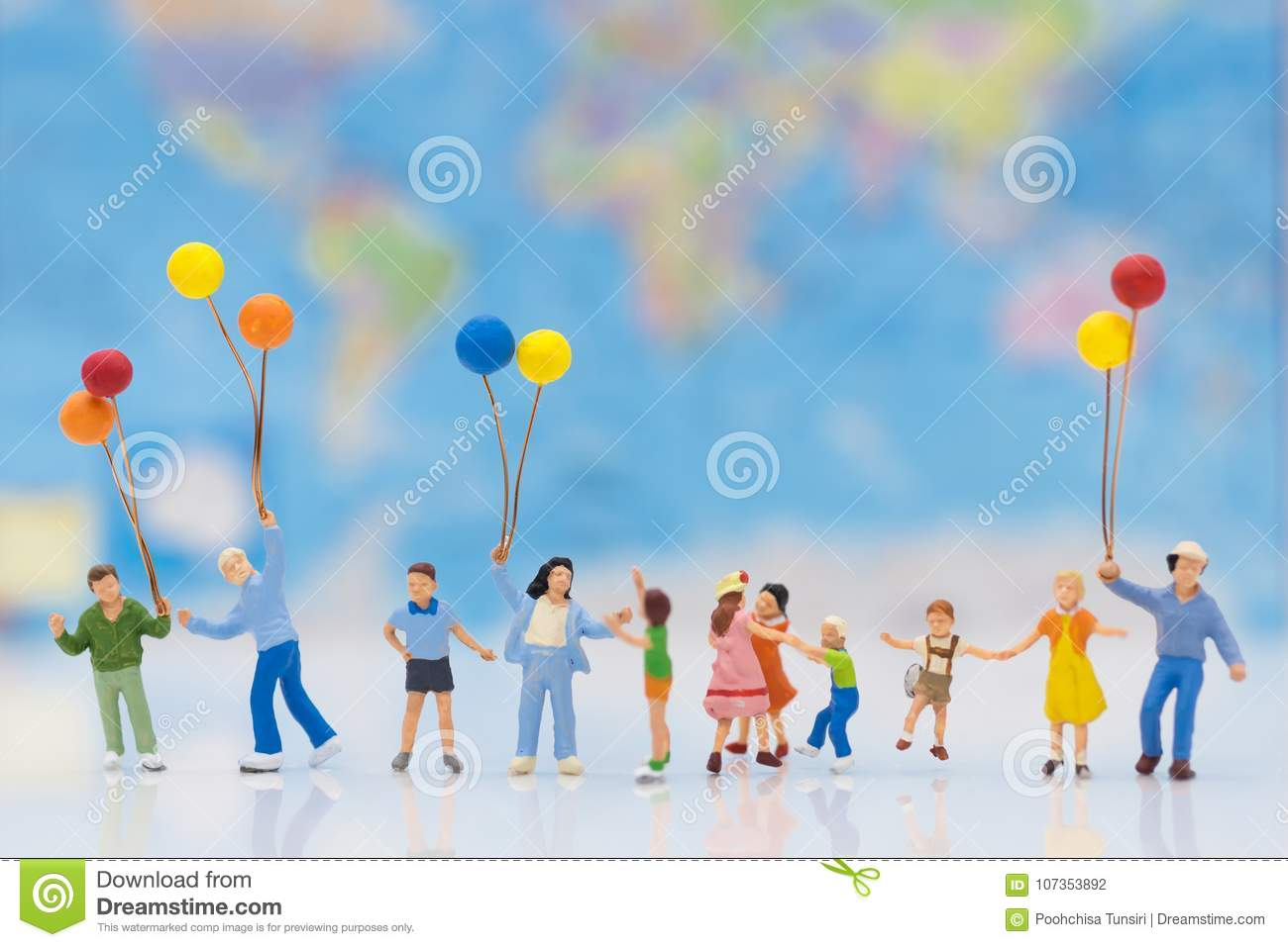 Miniature people: children hold balloons, and play together, background is map of world,