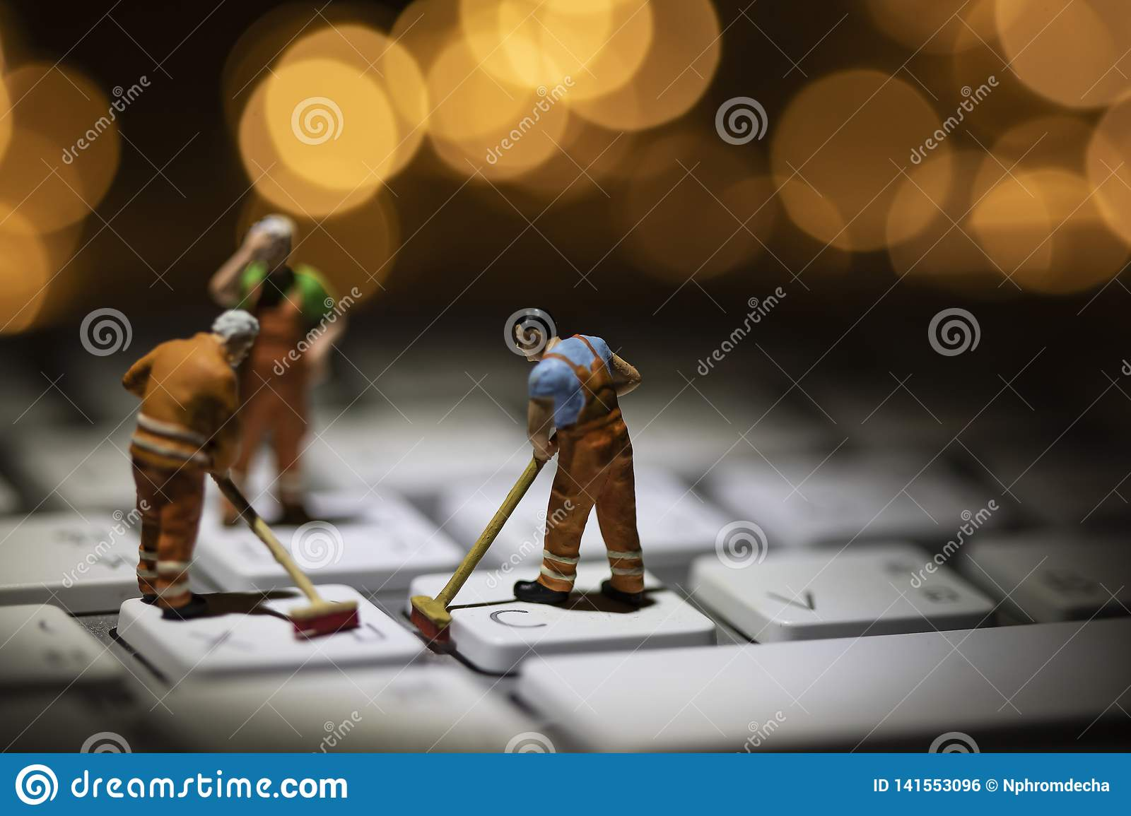 Miniature people cleaning white keyboard computer