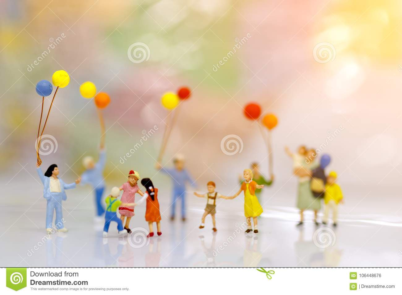Miniature people, family and children with colorful balloons standing in front of house,