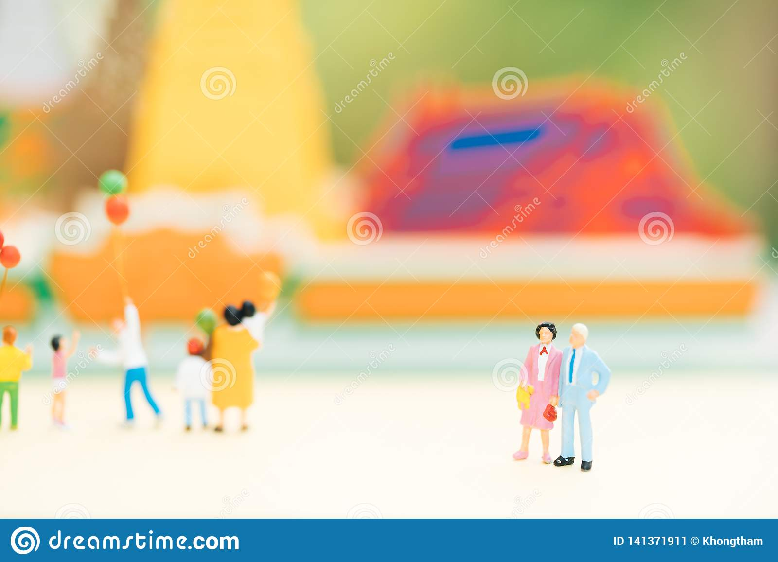 Miniature people: Old couple figure standing in front of temple with others tourist