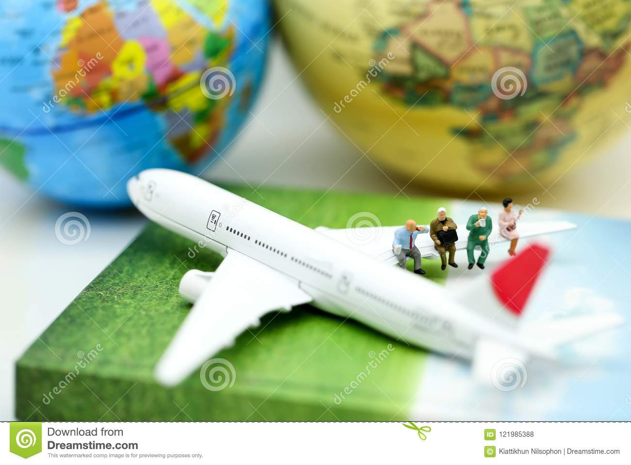 Miniature people : sitting on airplane wing for travel around th