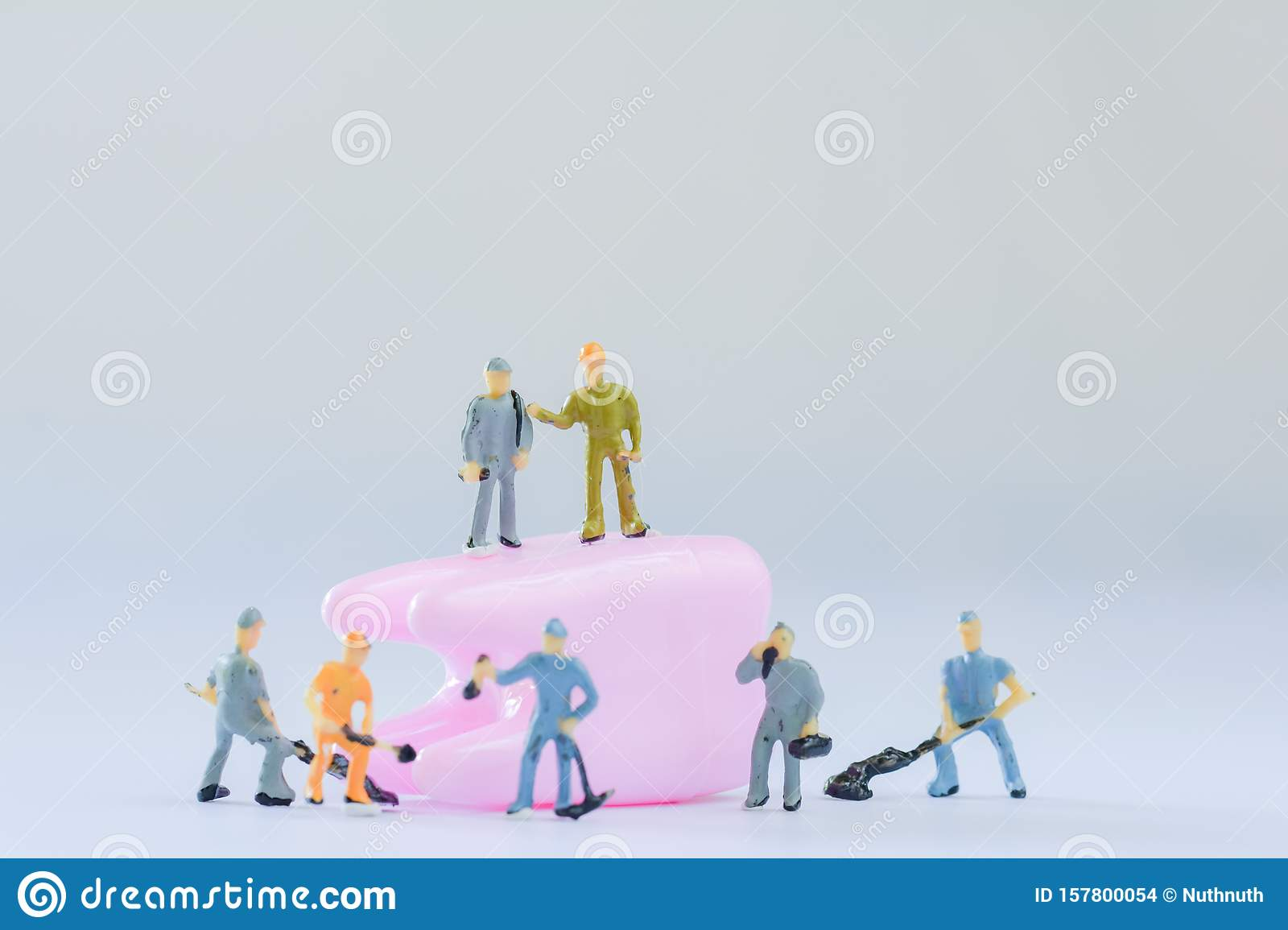 Miniature people, small model human figure clean pink tooth with copy space. Medical and dental concept. Team work on dental care.