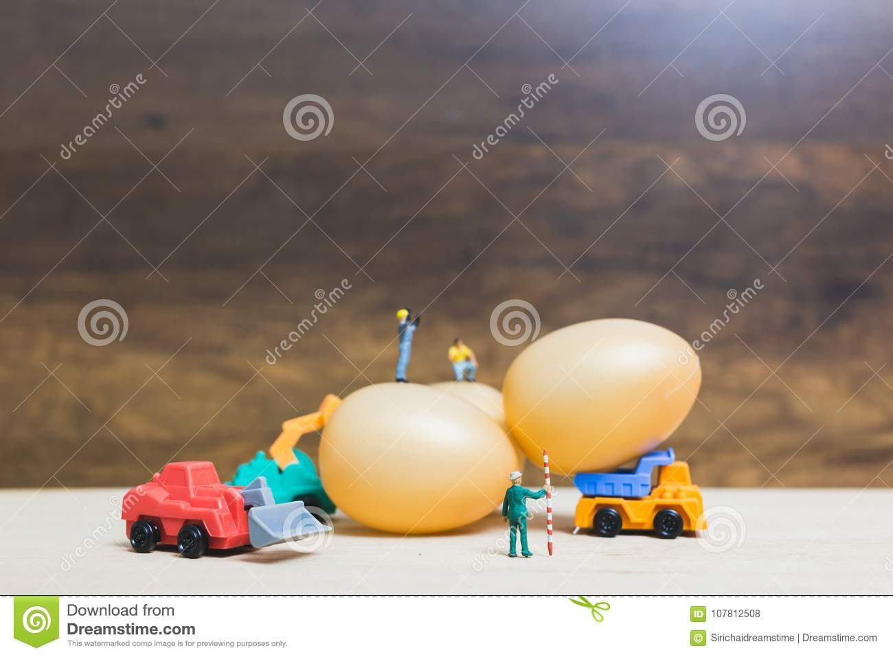 Miniature people work at Easter-eggs for Easter day