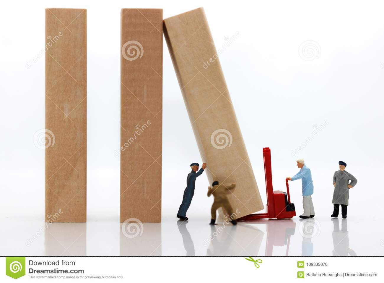 Miniature people: Workers team stopping the domino effect,
