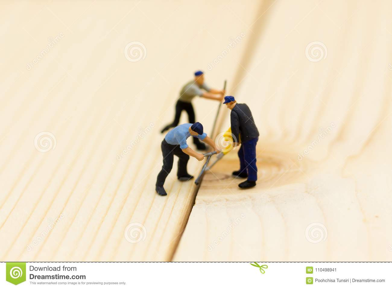 Miniature people: Workers are using wood punching equipment. Image use for construction work, business concept