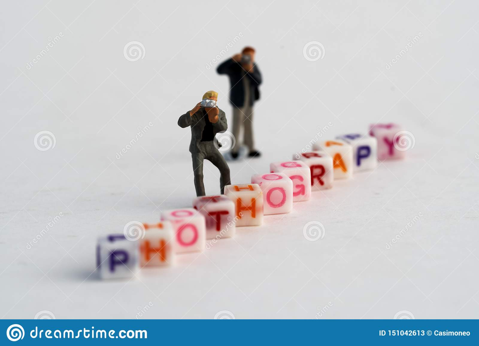 Miniature Photographers taking pictures behind a Group Of Letters forming Word Spelling