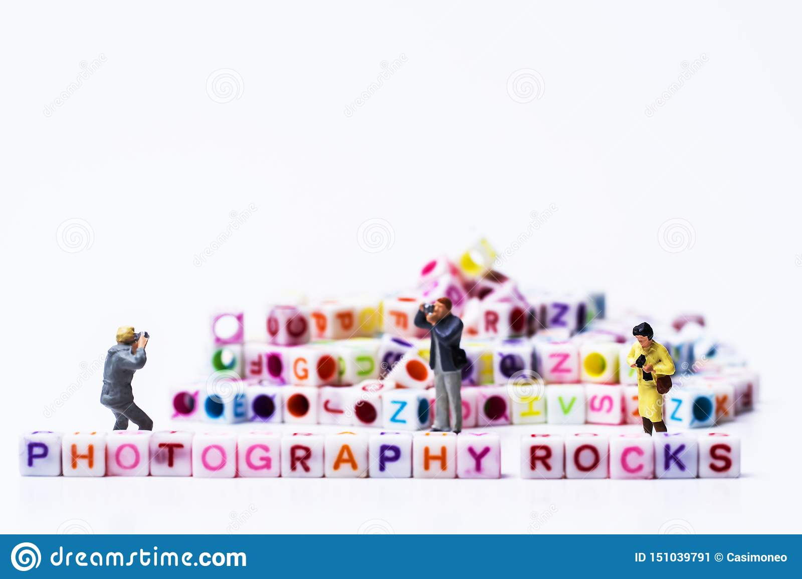 Miniature Photographers taking pictures before a Group Of Letters forming Words Spelling