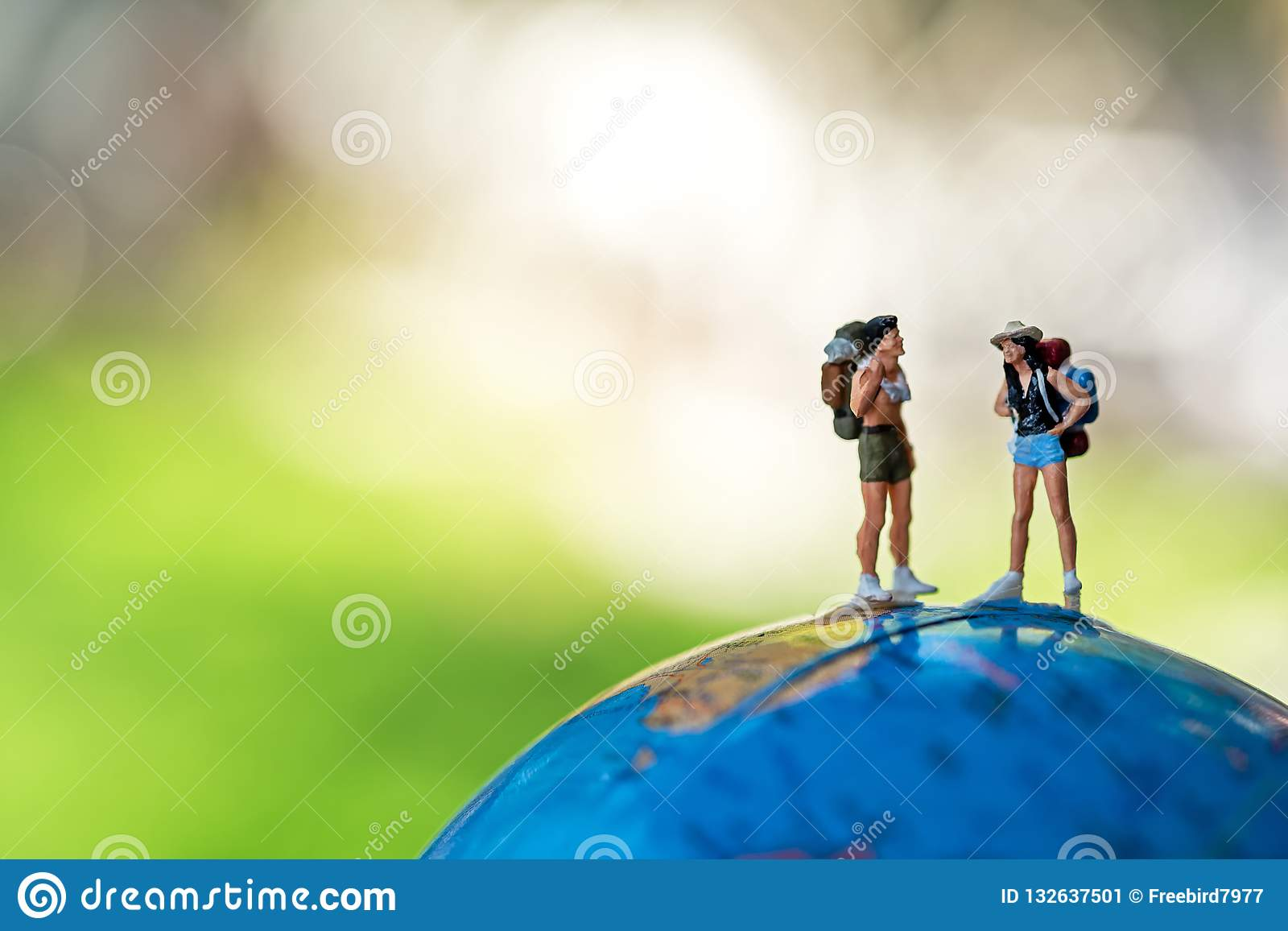 Miniature traveler and hiker backpack standing on the globe for the tourist and adventure around the world for vacations trip.