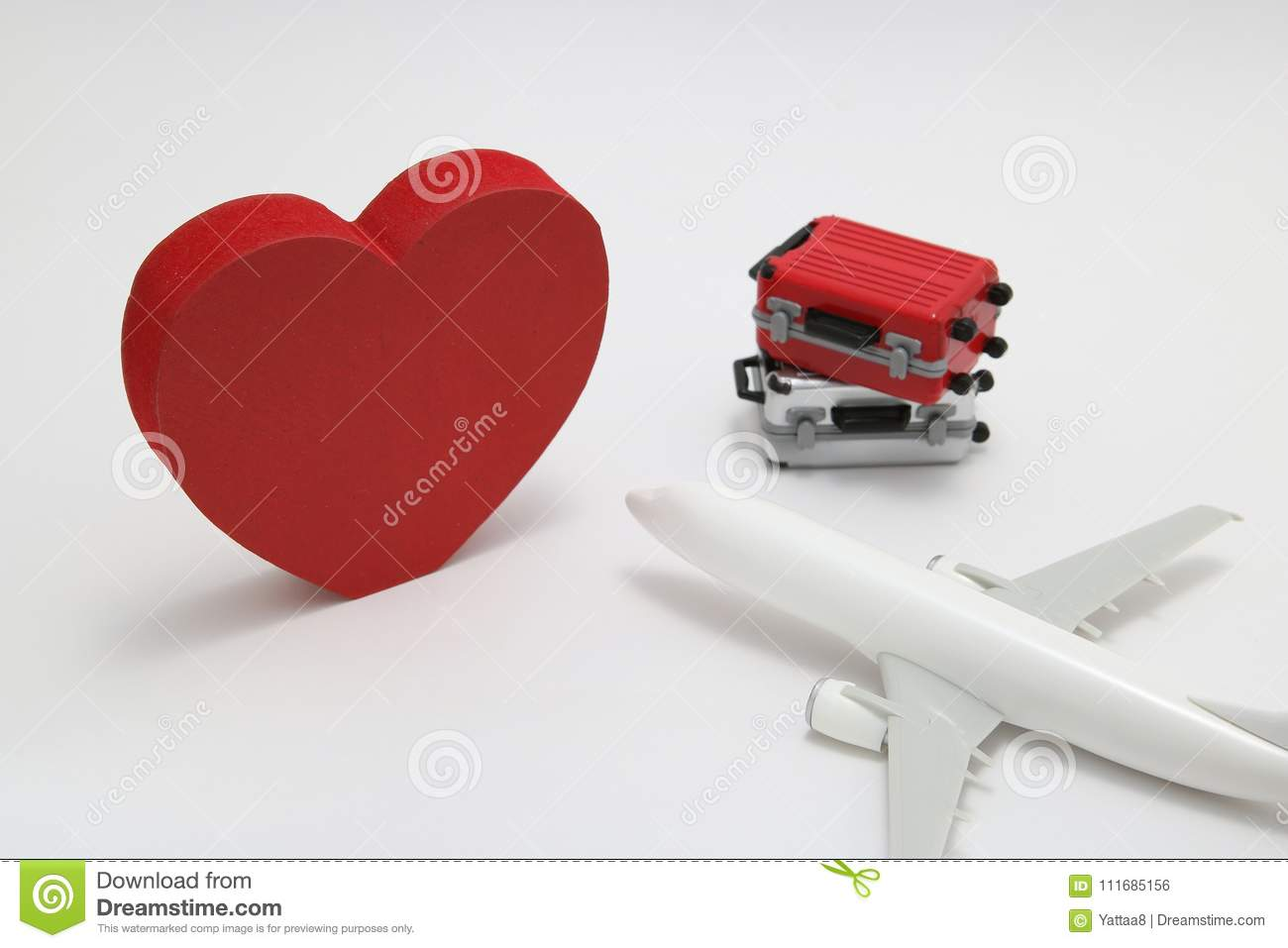 Miniature two suitcases, toy airplane, and a red heart on white background.