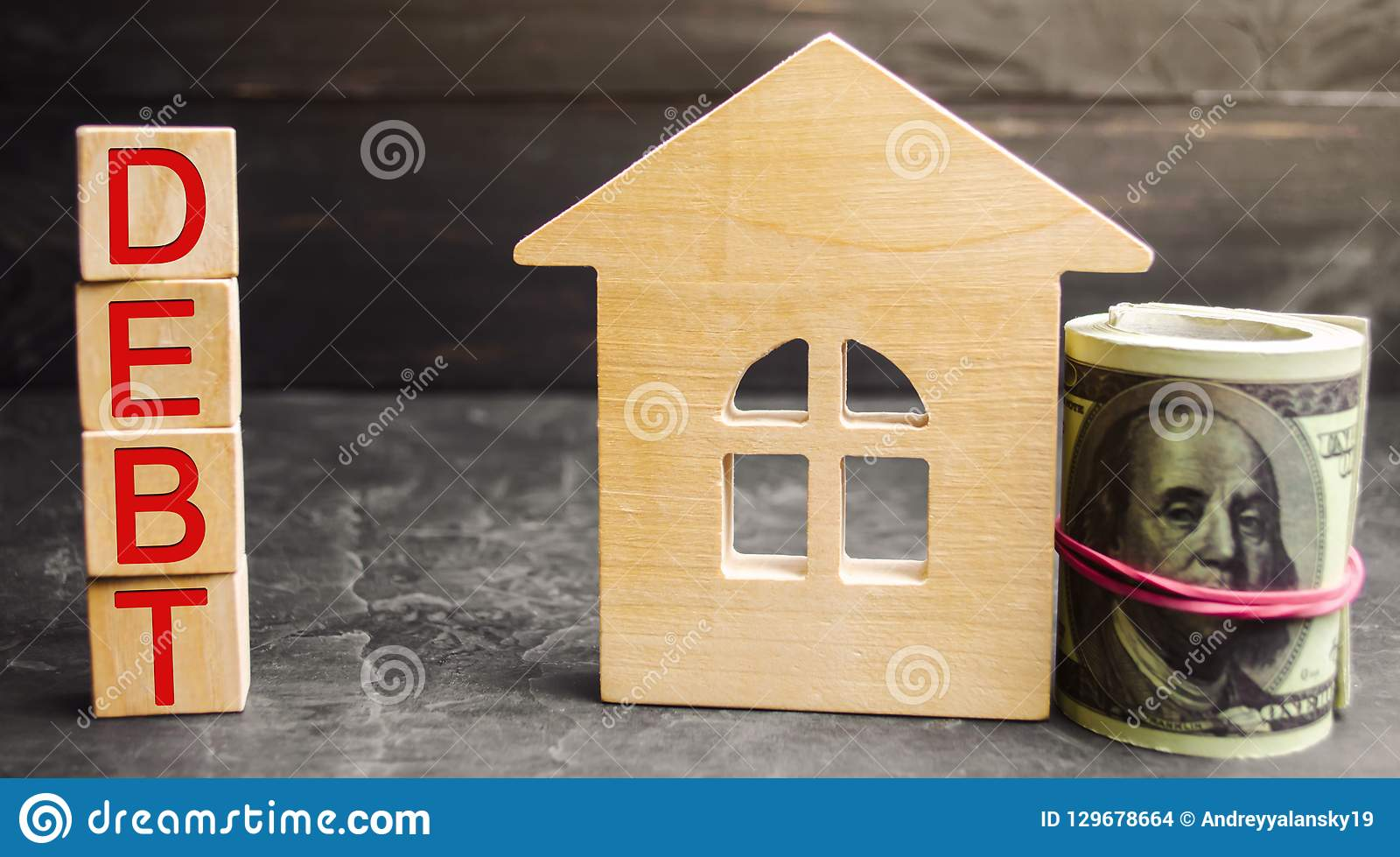 Miniature wooden house, dollars and the inscription ` Debt `. Real estate, home savings, loans market concept. Payment of real est