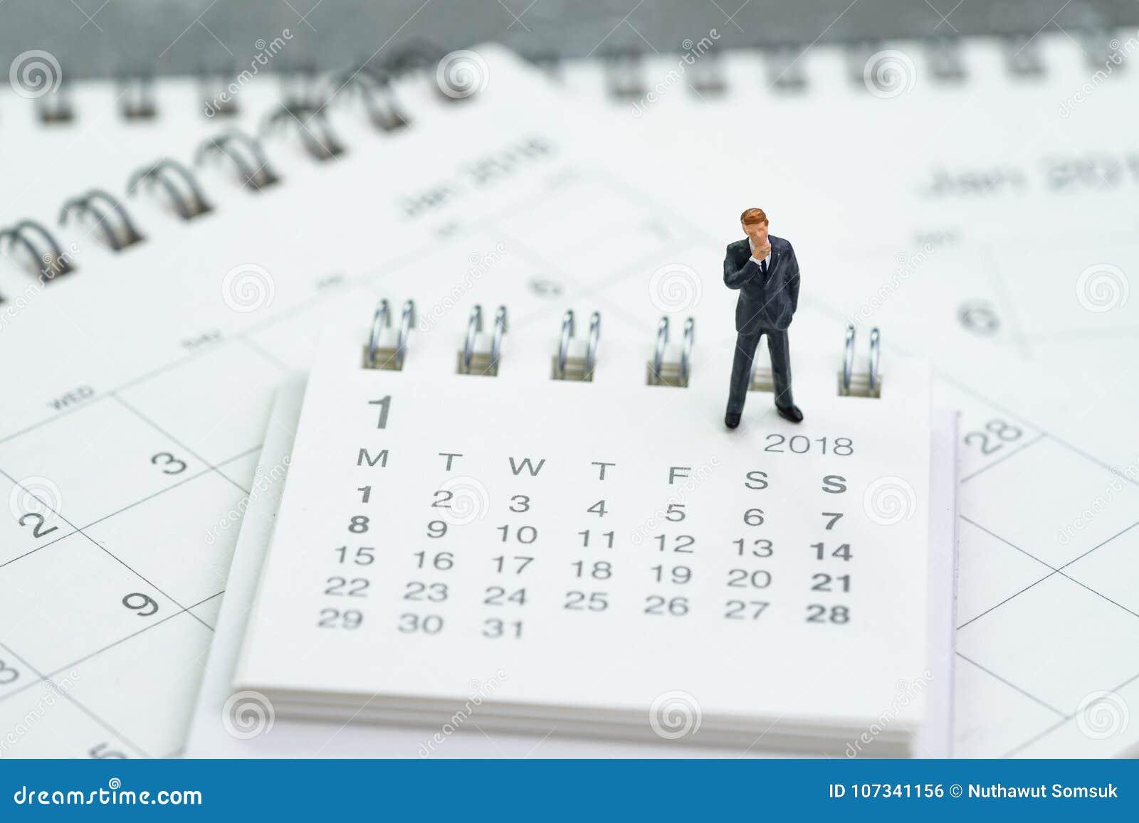 Miniaturgeschäftsmann, der auf Kalendern unter Verwendung a denkt und steht