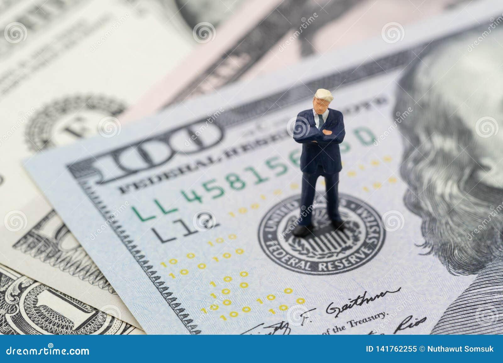 Miniaturgeschäftsmannführerstellung und das Denken auf Emblem US Federal Reserve auf US-Dollars Banknote als FED betrachten Inter