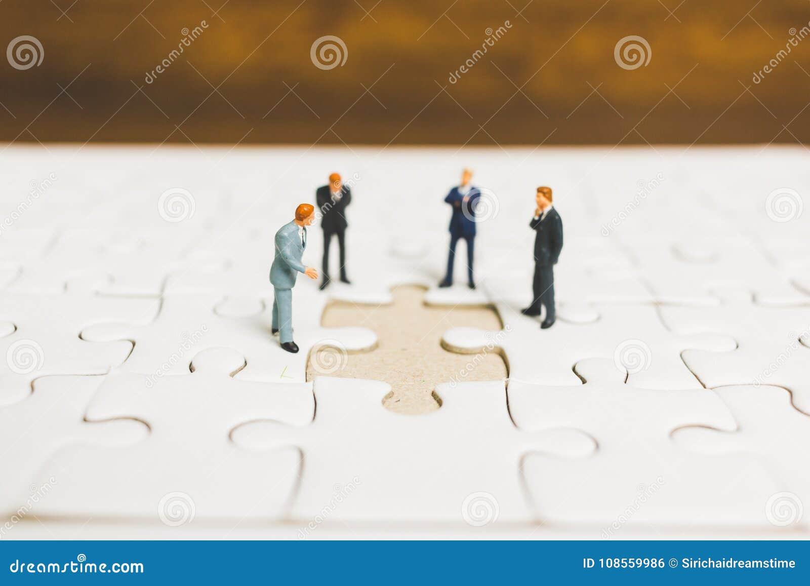 Miniaturleute: Geschäftsmann, der auf Laubsäge steht