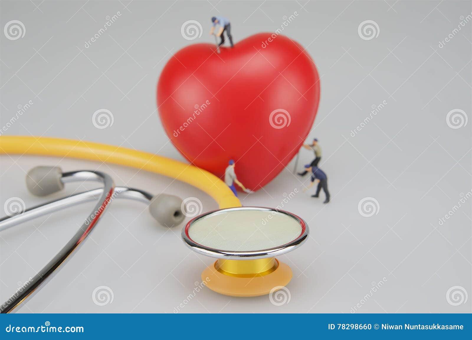 Miniaturleute und rotes Herz nahe Stethoskop