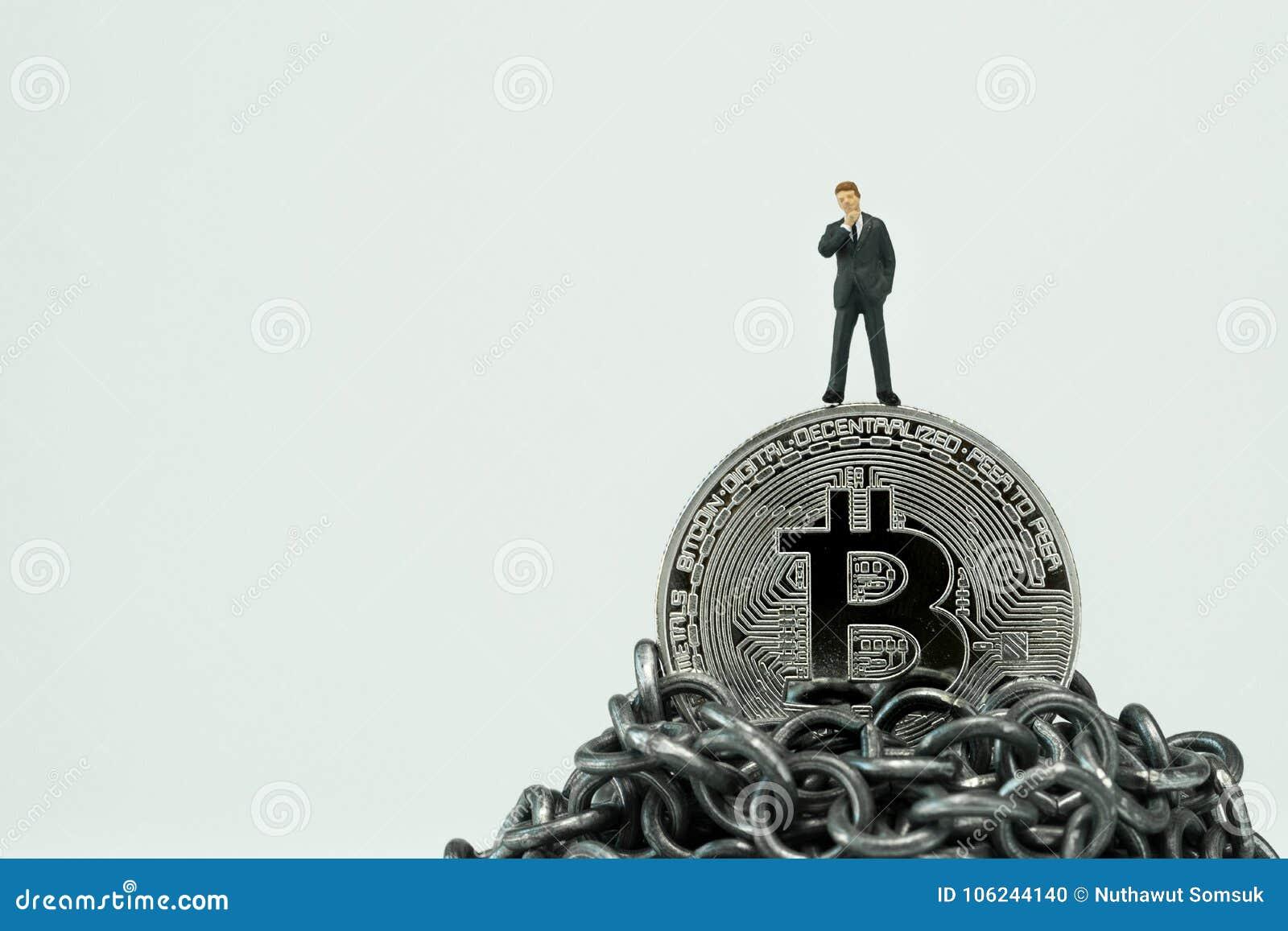 Miniaturowa biznesmen pozycja na Bitcoin na górze łańcuszkowego mounta