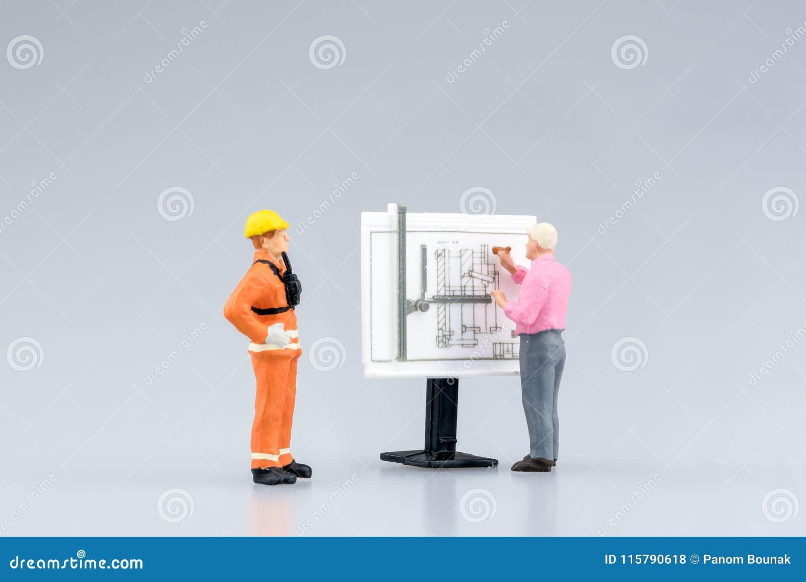 Miniaturowi inżynierii ludzie, architektura pracuje na budowa rysunku i