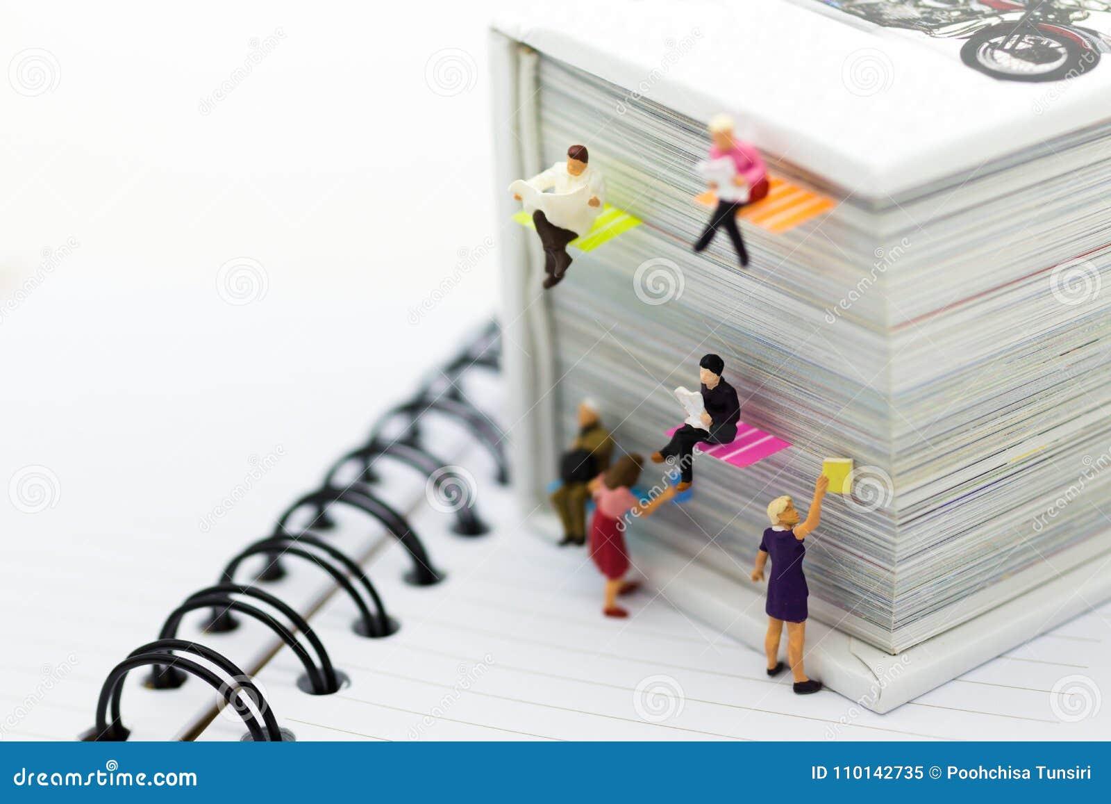 Miniaturowi ludzie: biznesmen czytelnicza gazeta na dużej książce Wizerunku use dla tło edukaci lub biznesu pojęcia