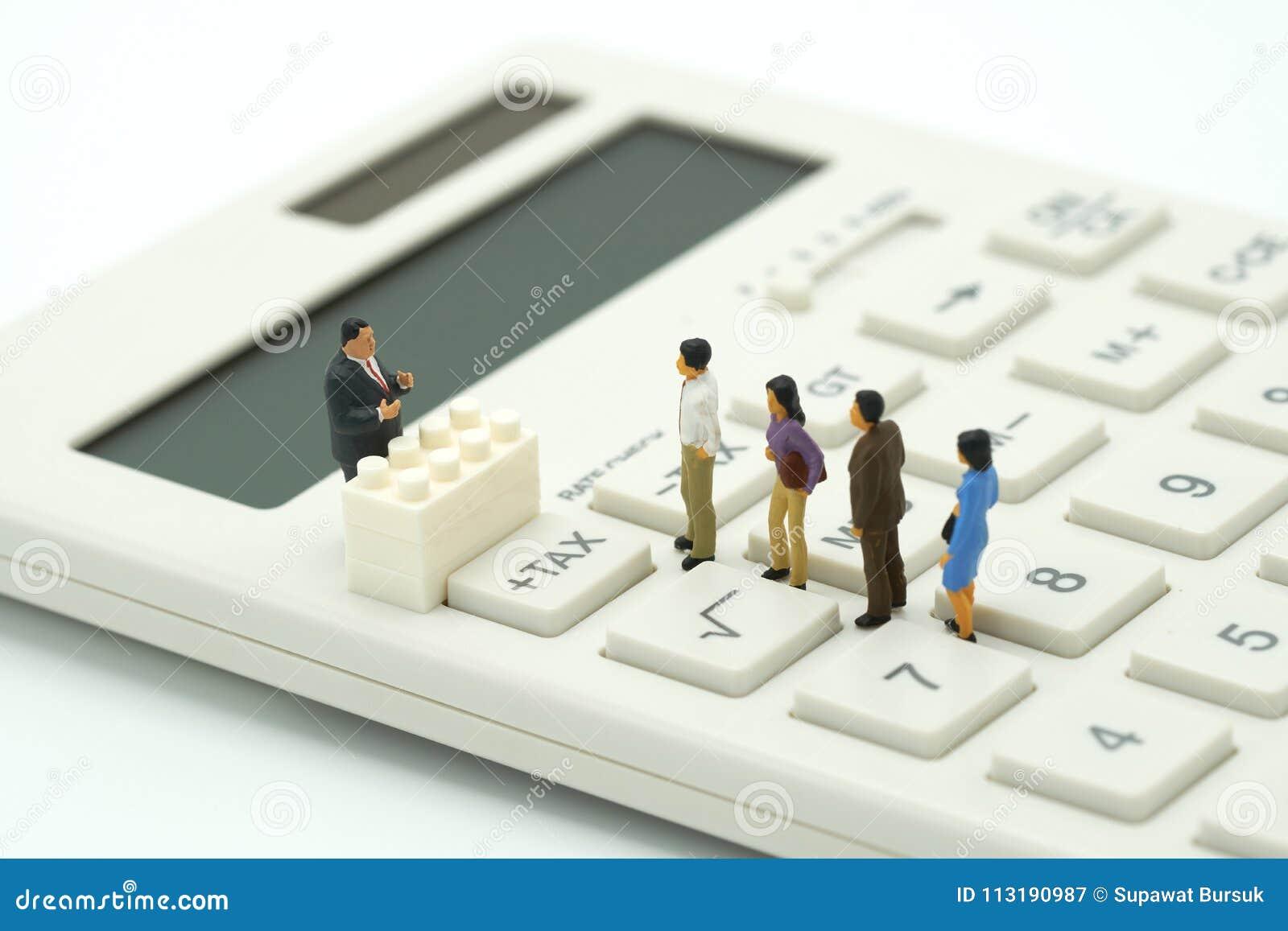 Miniaturowi ludzie Płacą kolejka rocznego dochodu podatek dla roku na kalkulatorze używać jako tła biznesowy pojęcie i finanse co