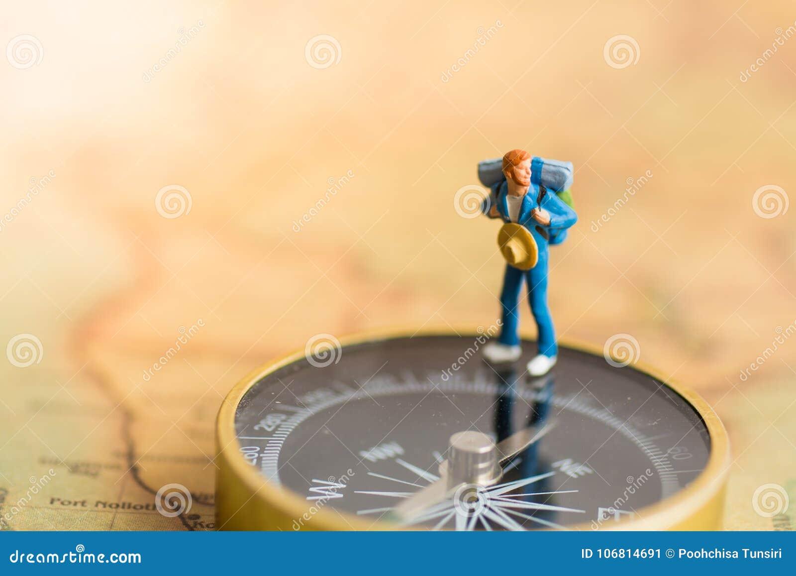Miniaturowi ludzie: podróżnika stojak mówić kierunek podróż na kompasie Use jako biznesowej podróży pojęcie